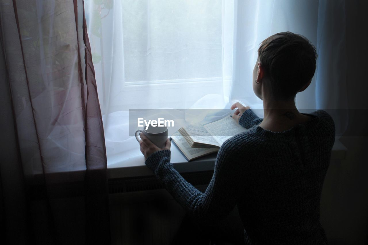 High Angle View Of Woman Holding Coffee Cup While Reading Book On Window Sill