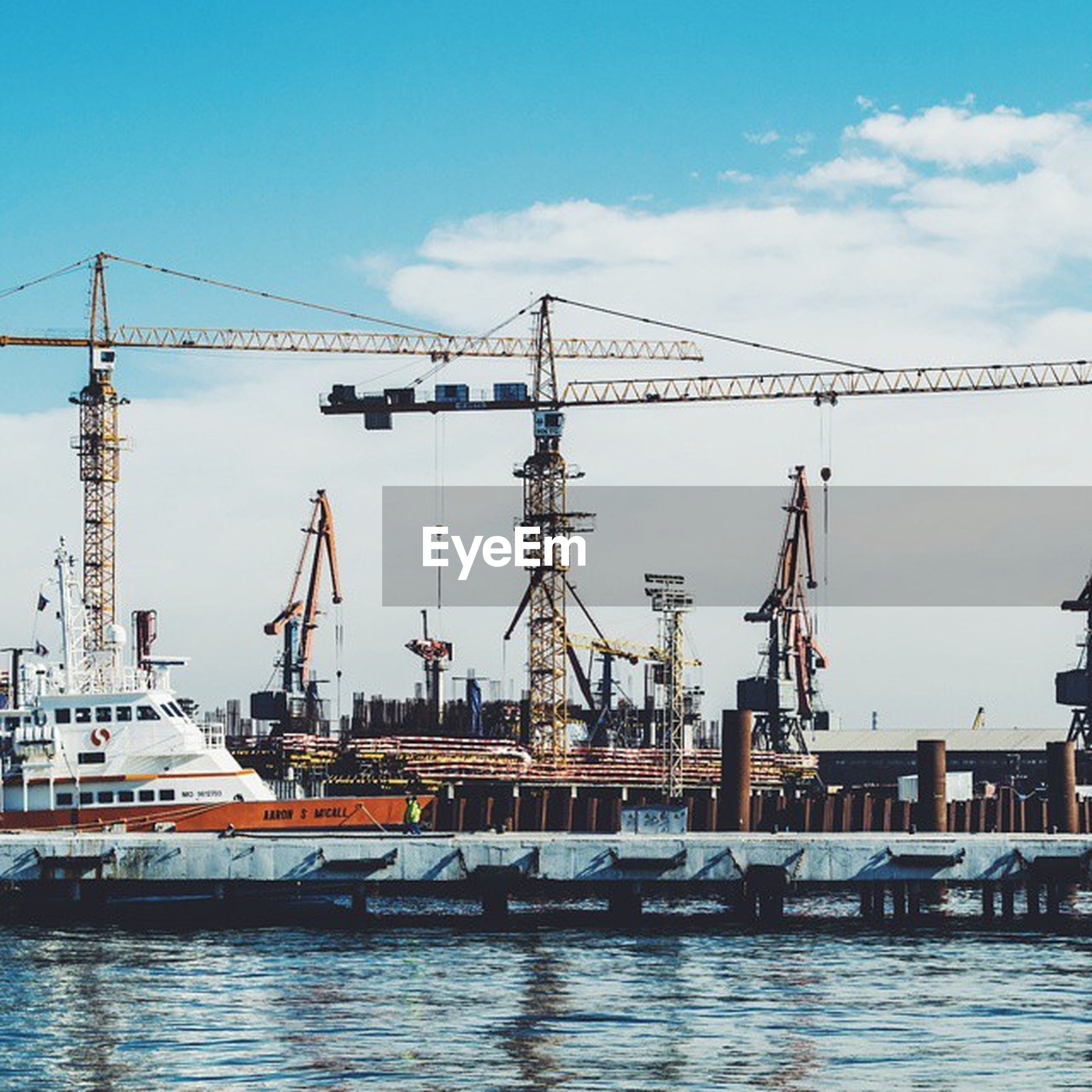 water, harbor, nautical vessel, commercial dock, sky, waterfront, built structure, mast, crane - construction machinery, architecture, building exterior, moored, transportation, fuel and power generation, crane, boat, mode of transport, ship, cloud - sky, day