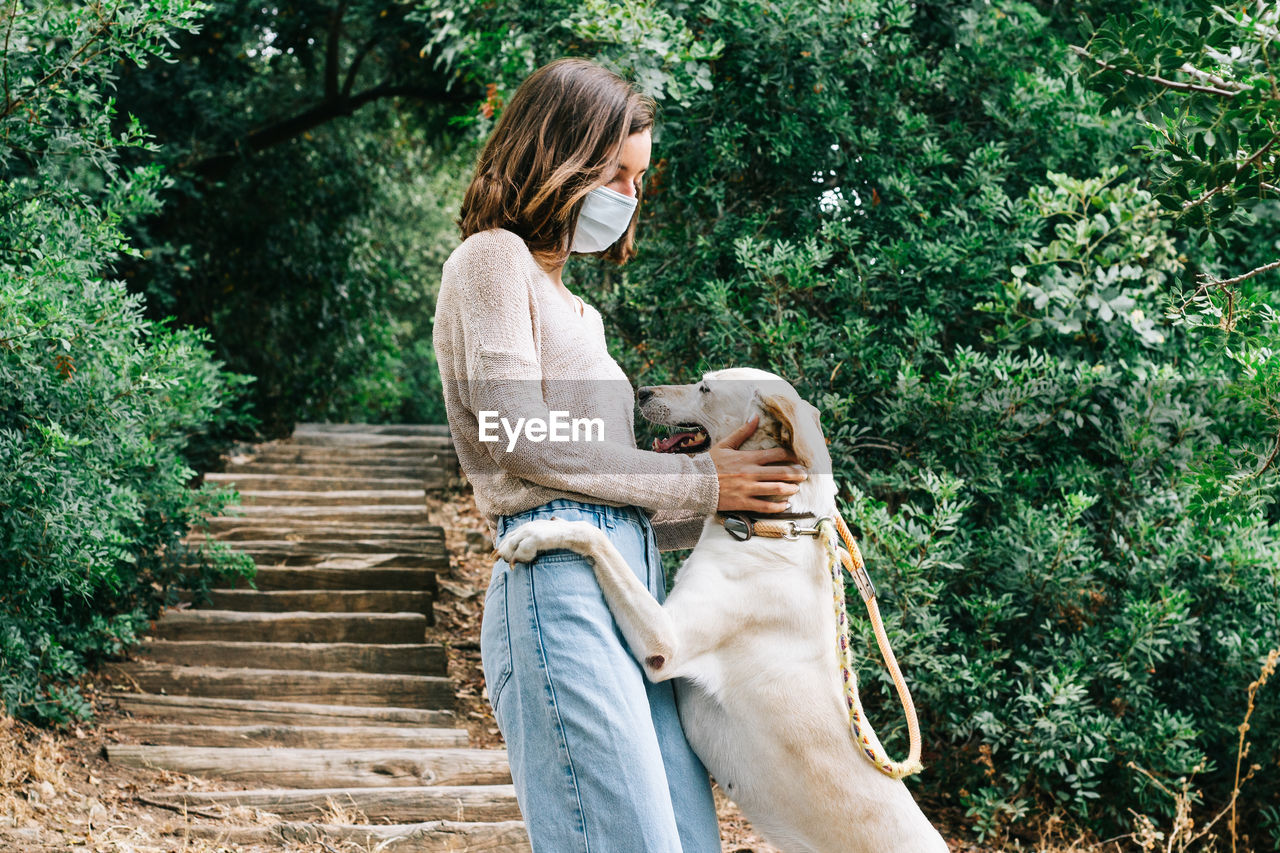 Young woman wearing a face mask caressing a dog playing in the park. concept of new normal outdoors.