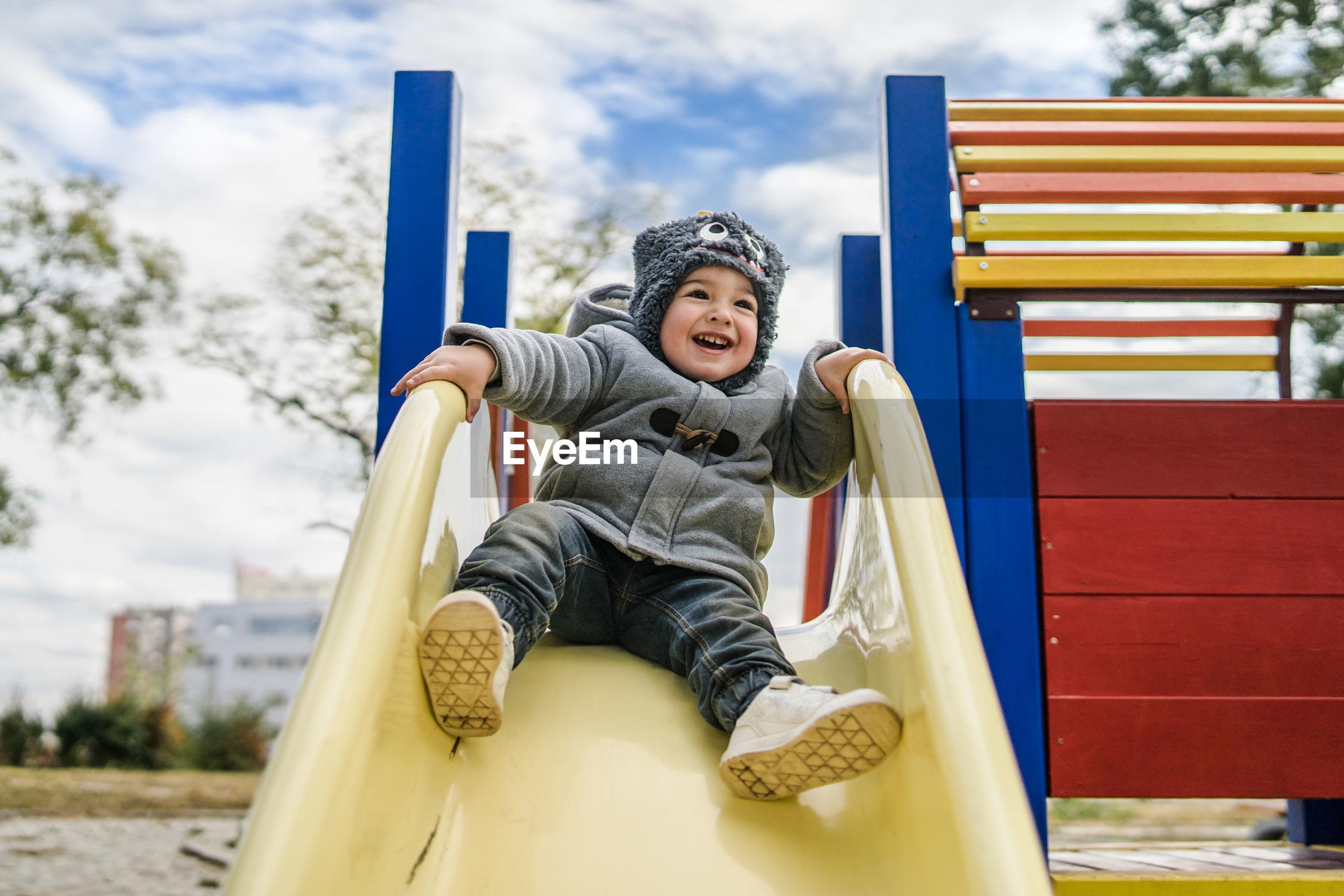 Cheerful boy sitting on slide at playground