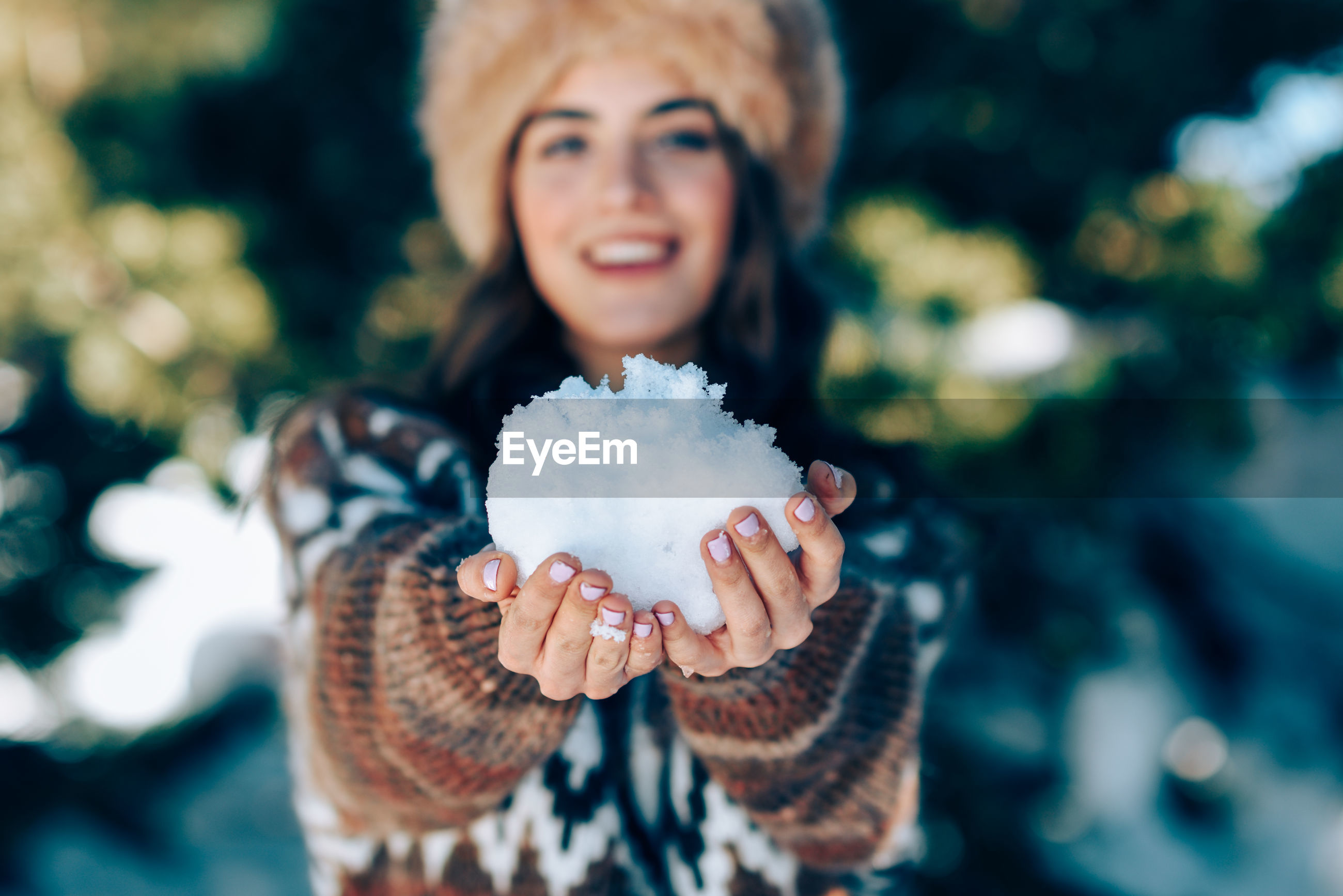 Portrait of smiling young woman holding snow during winter