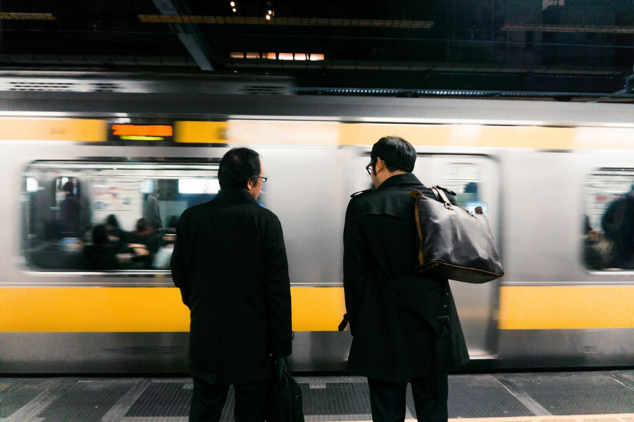 Rear view of men standing at subway station