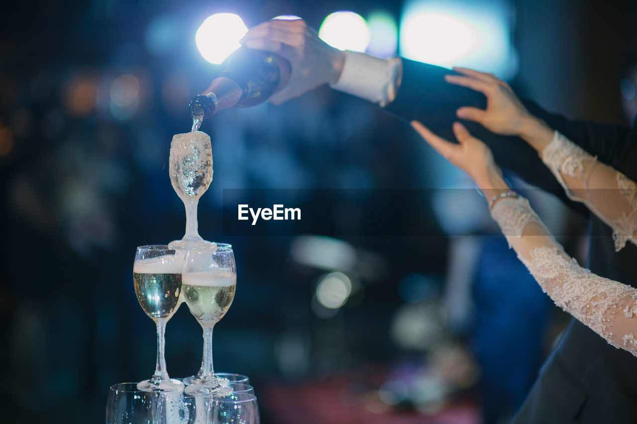 Cropped Hands Of Newlywed Couple Pouring Wine In Glasses At Wedding Ceremony