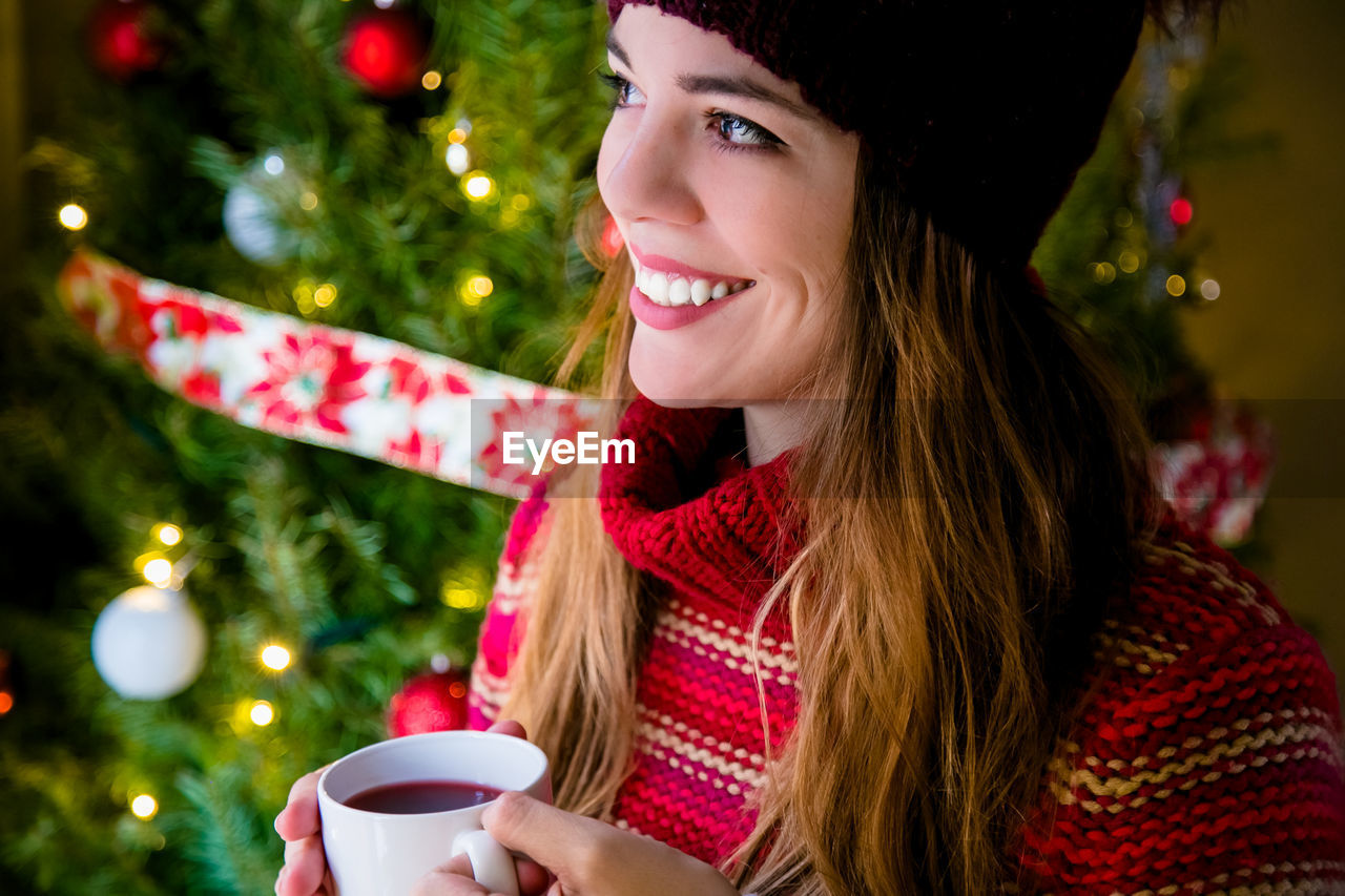 YOUNG WOMAN DRINKING COFFEE CUP ON TREE