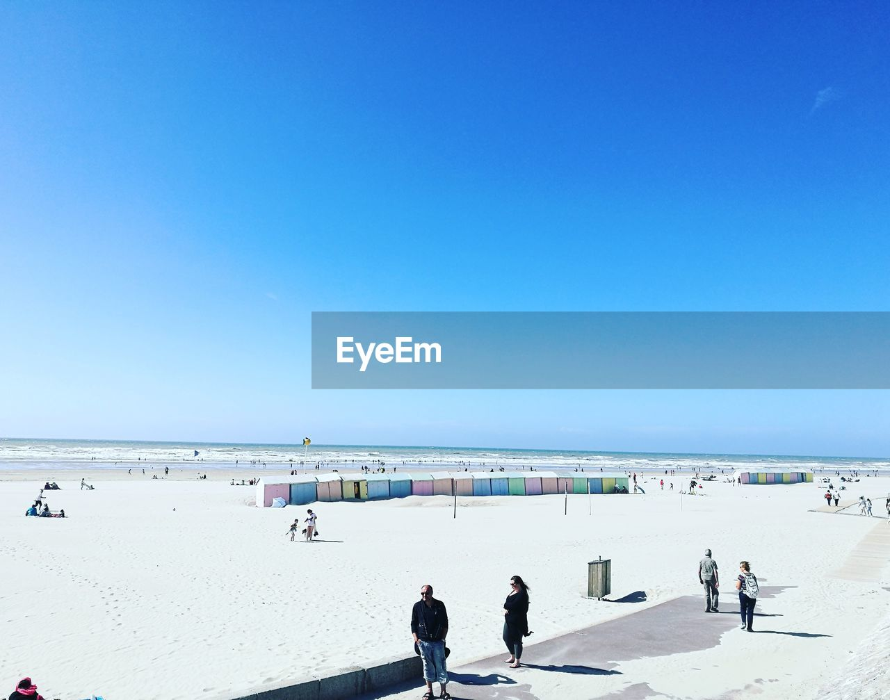 People walking on beach against clear blue sky