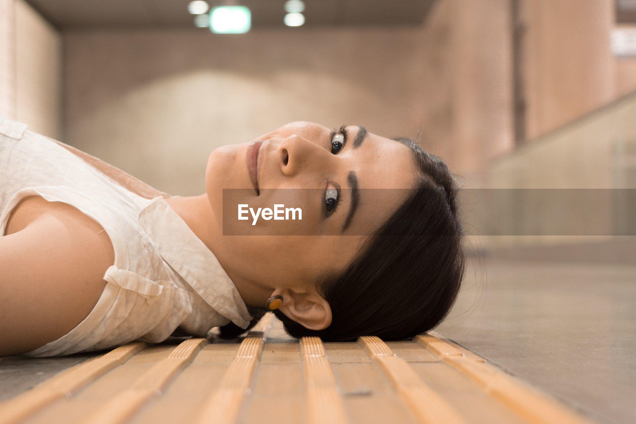 Portrait of young woman lying on floor