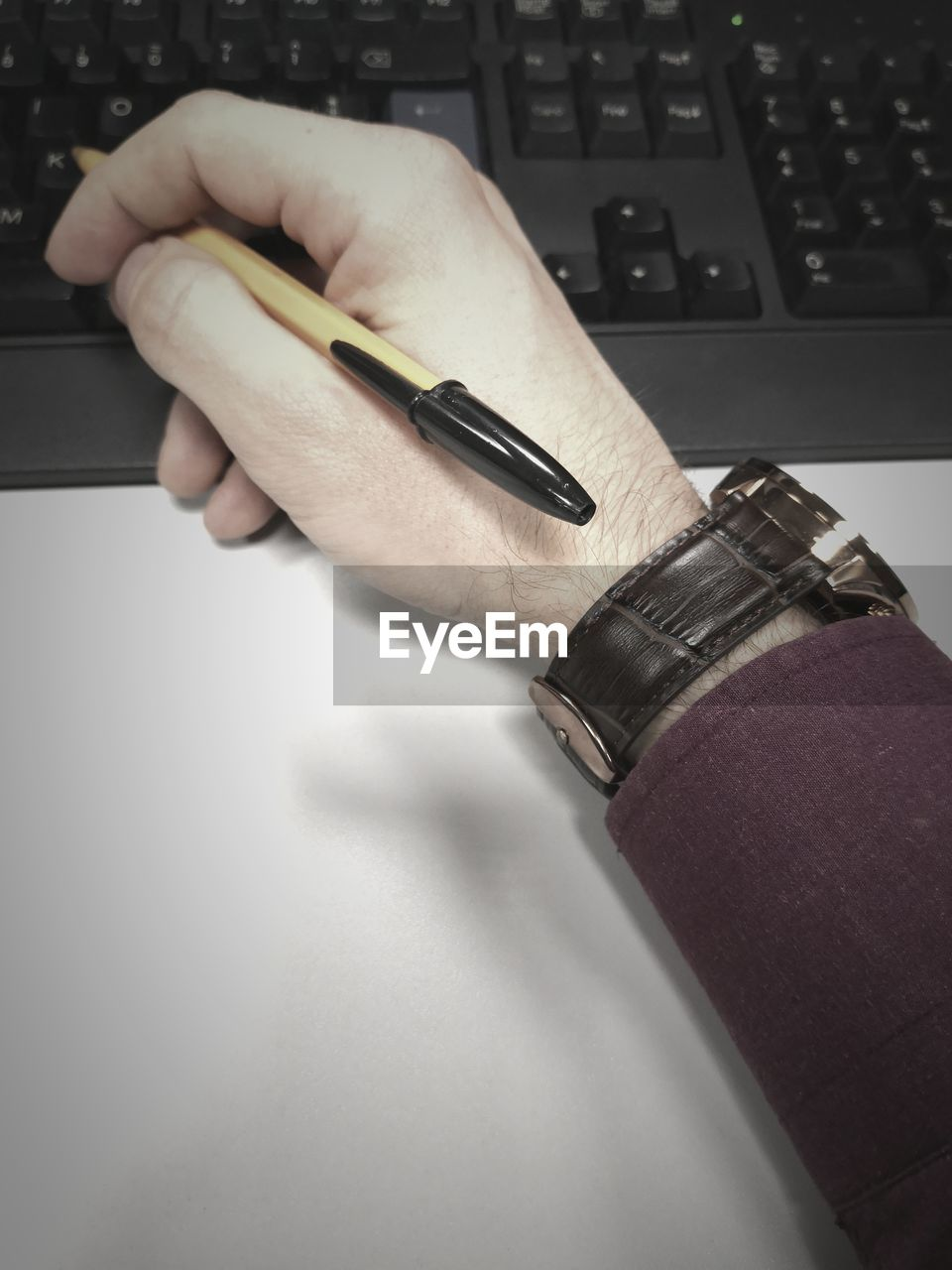 human hand, hand, one person, human body part, indoors, real people, pen, computer, body part, technology, holding, table, laptop, wireless technology, communication, high angle view, connection, close-up, writing instrument, finger, human limb, keyboard