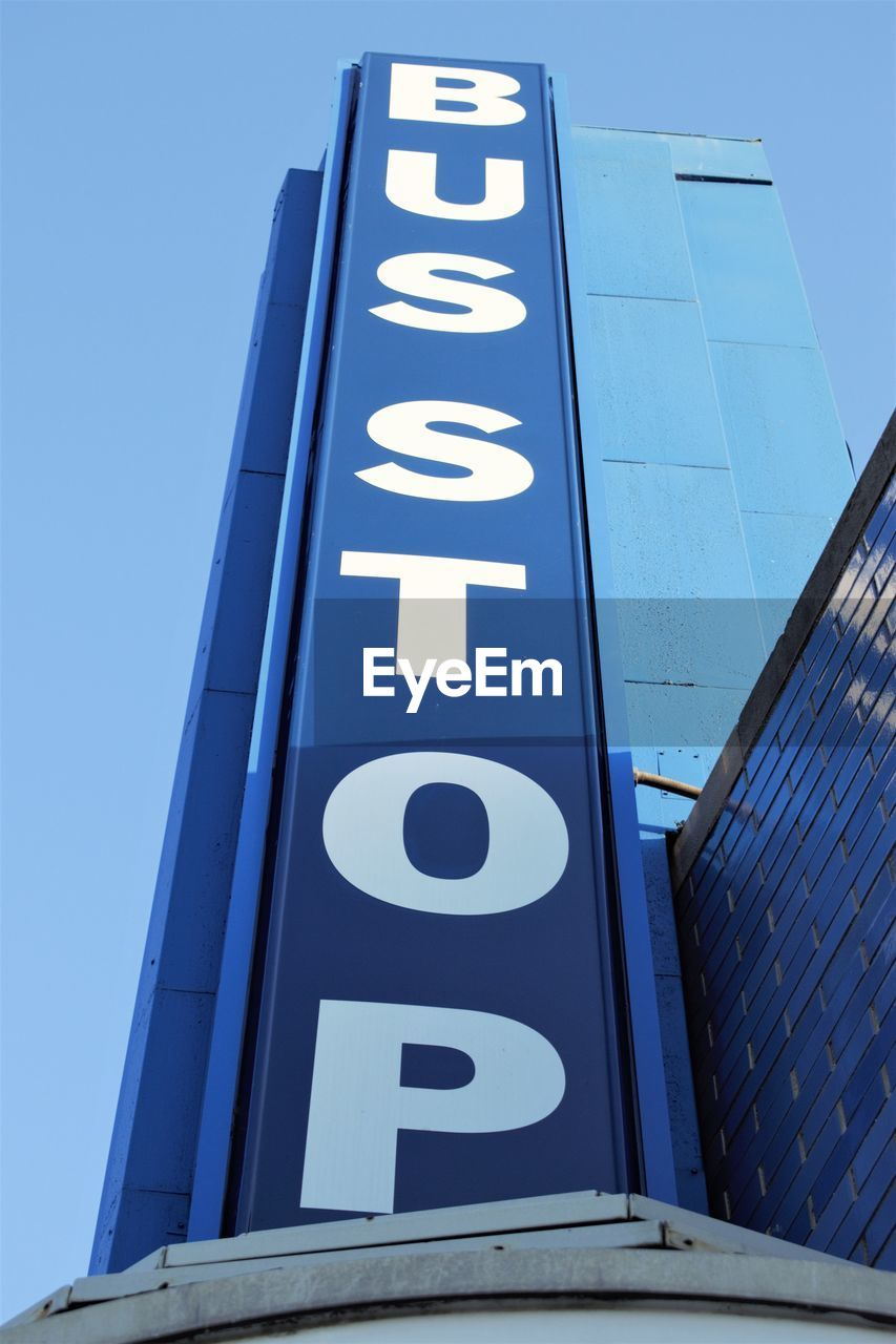 communication, low angle view, built structure, building exterior, architecture, no people, text, western script, capital letter, number, sky, day, clear sky, city, sign, blue, office building exterior, outdoors, tall - high, information, skyscraper