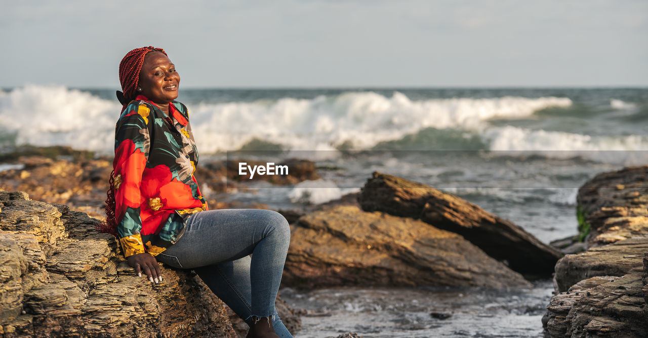 African woman sitting on the beach cliffs at sunset in accra ghana west africa