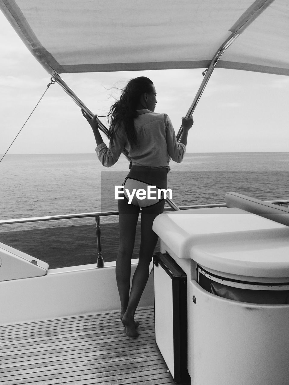 Rear view of woman standing at boat deck on sea