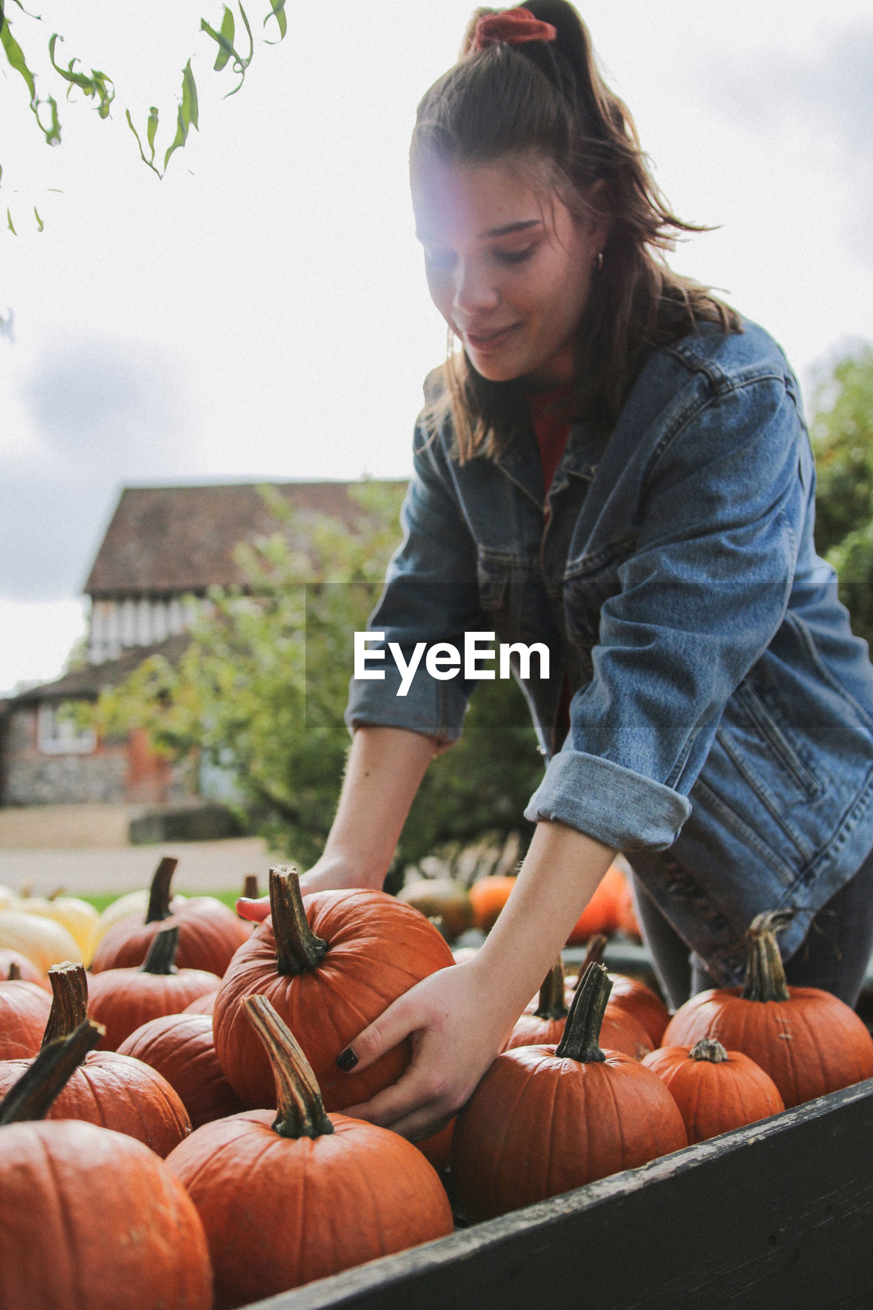 Young woman standing by pumpkins