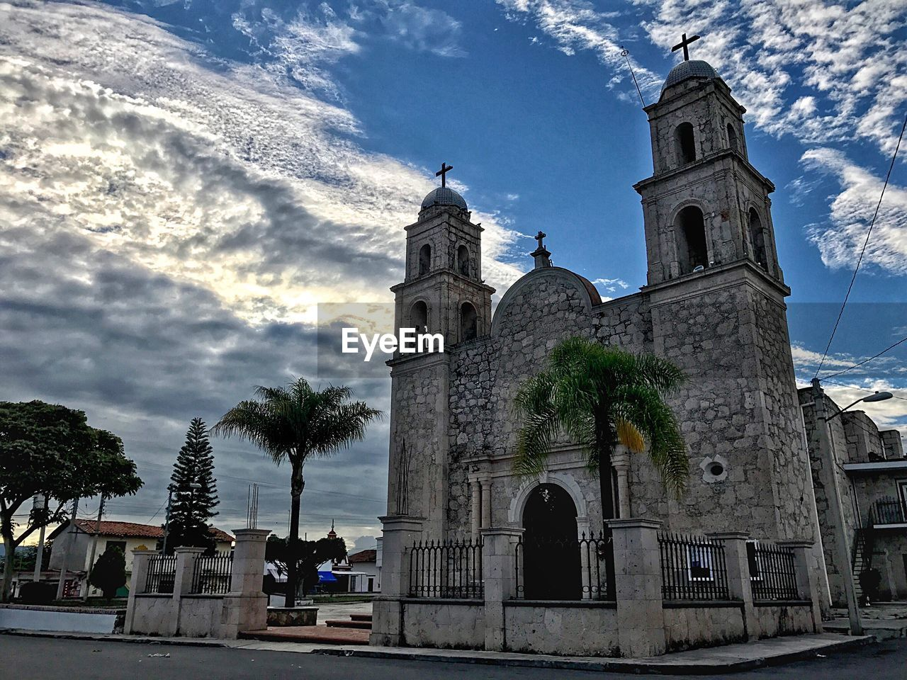 religion, place of worship, spirituality, architecture, building exterior, built structure, sky, cloud - sky, cross, bell tower, day, outdoors, tree, low angle view, no people, travel destinations, sunlight