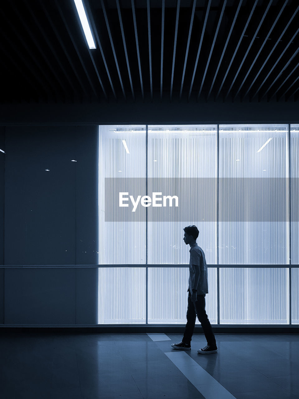 Side View Of Teenage Boy Walking By Window On Tiled Floor