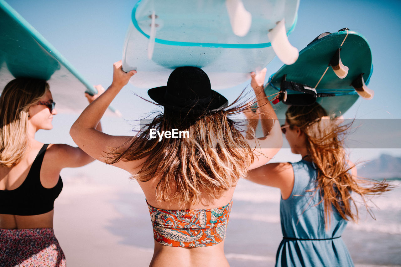 Rear View Of Female Friends Carrying Surfboards On Head At Beach