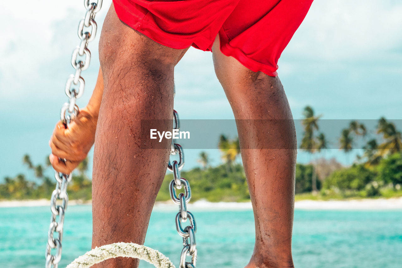 Midsection Of Man Pulling On Anchor Chain