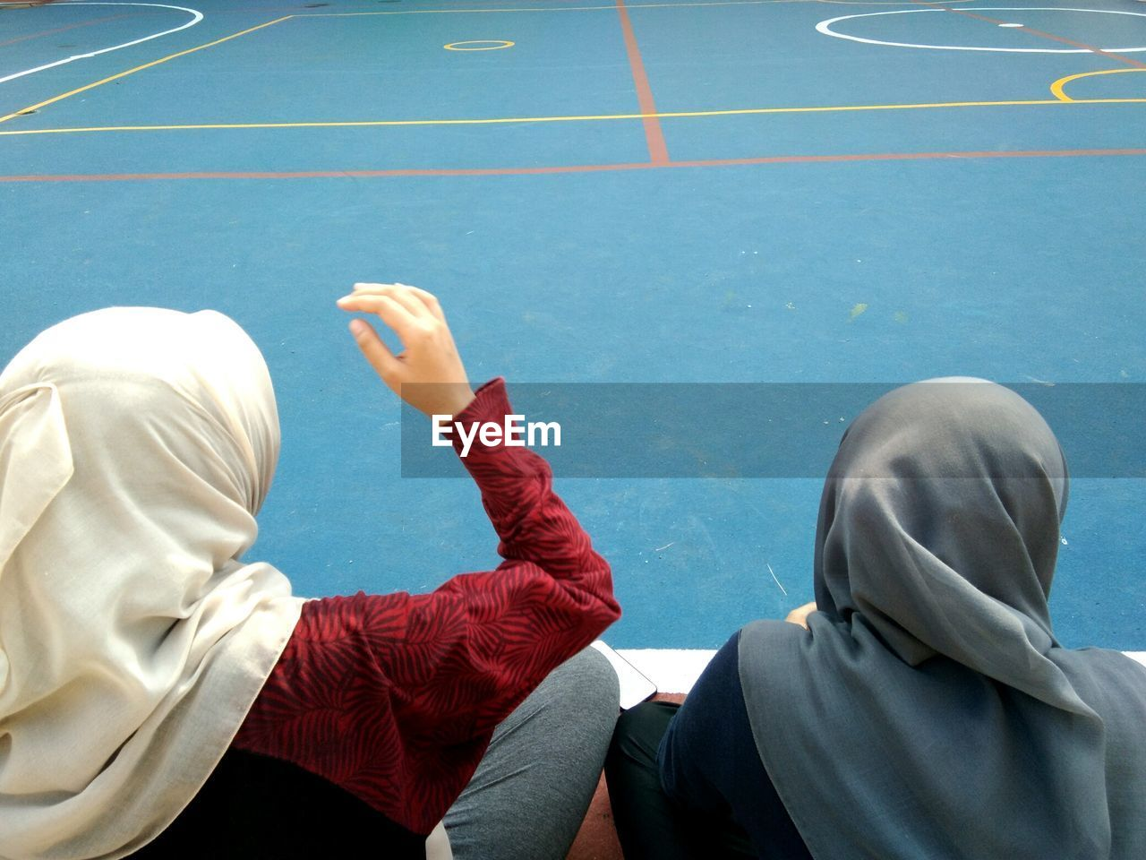 Rear View Of Female Friends Wearing Hijab On Court