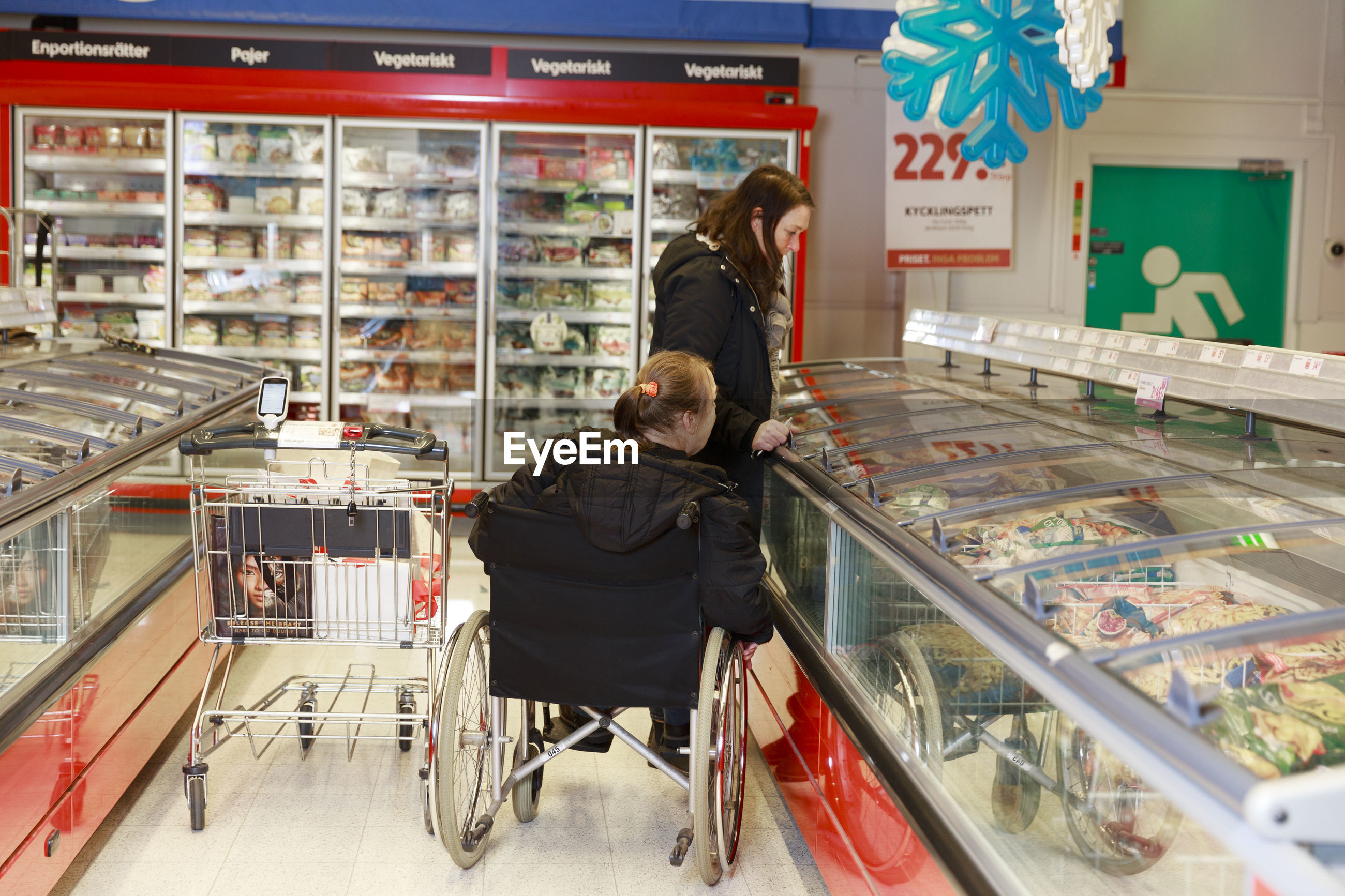 REAR VIEW OF MAN AND WOMAN SITTING IN STORE