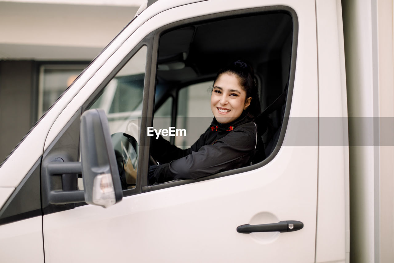 PORTRAIT OF A SMILING YOUNG WOMAN SITTING IN CAR