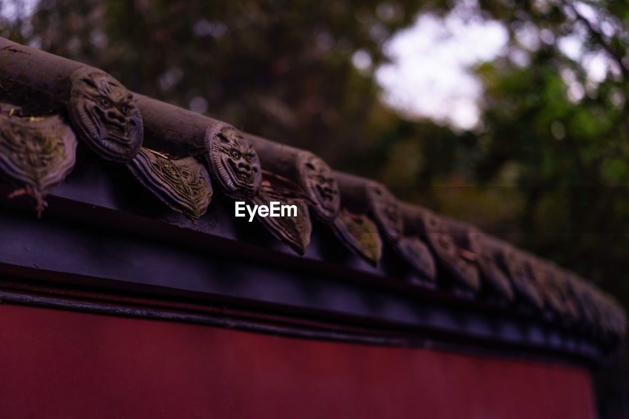 roof, no people, built structure, architecture, low angle view, day, focus on foreground, selective focus, place of worship, art and craft, building, pattern, outdoors, building exterior, craft, close-up, creativity, roof tile, wood - material, sky, ornate