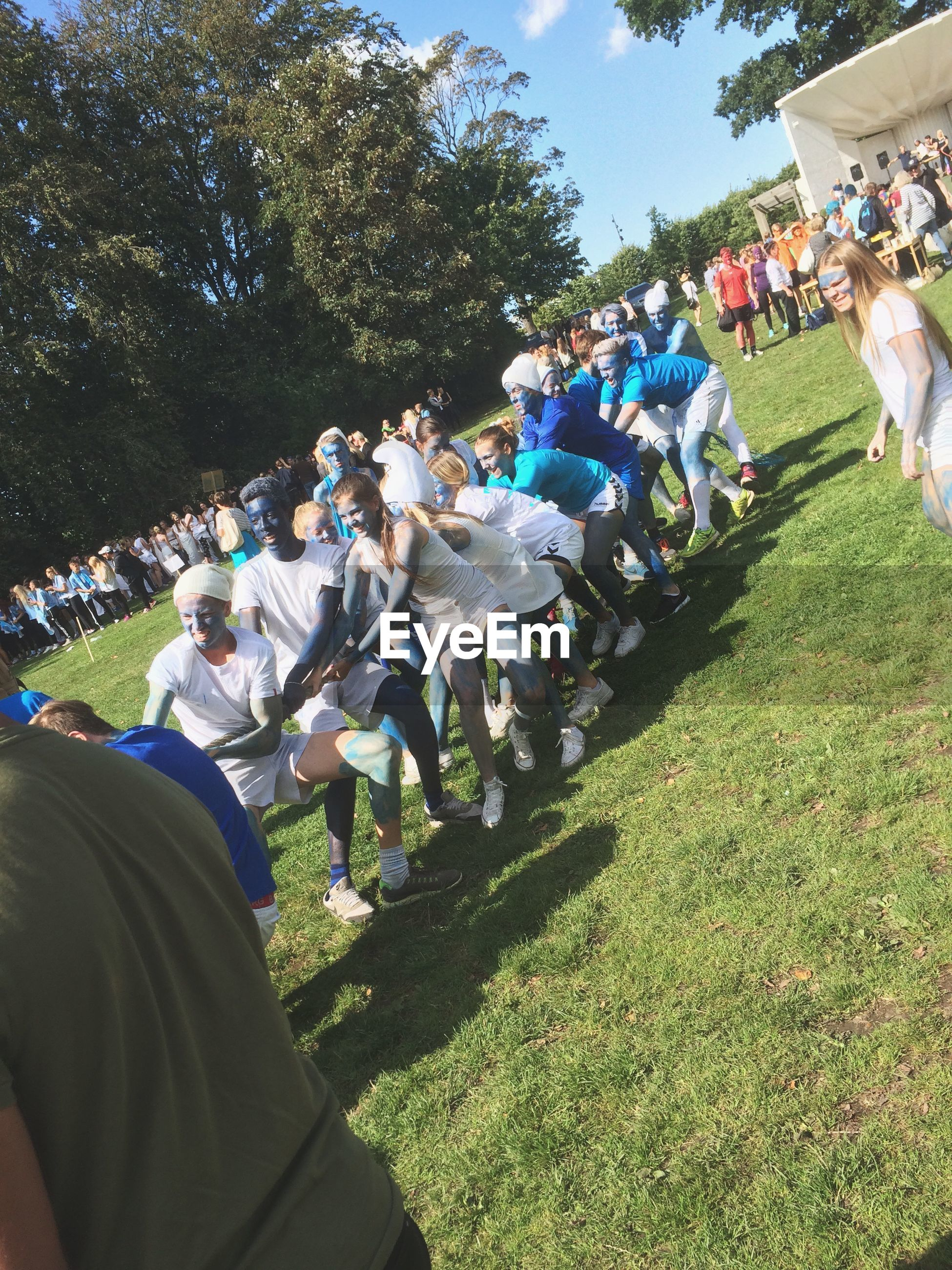 men, grass, leisure activity, lifestyles, sunlight, tree, person, green color, park - man made space, day, field, incidental people, blue, outdoors, large group of people, growth, nature, unrecognizable person