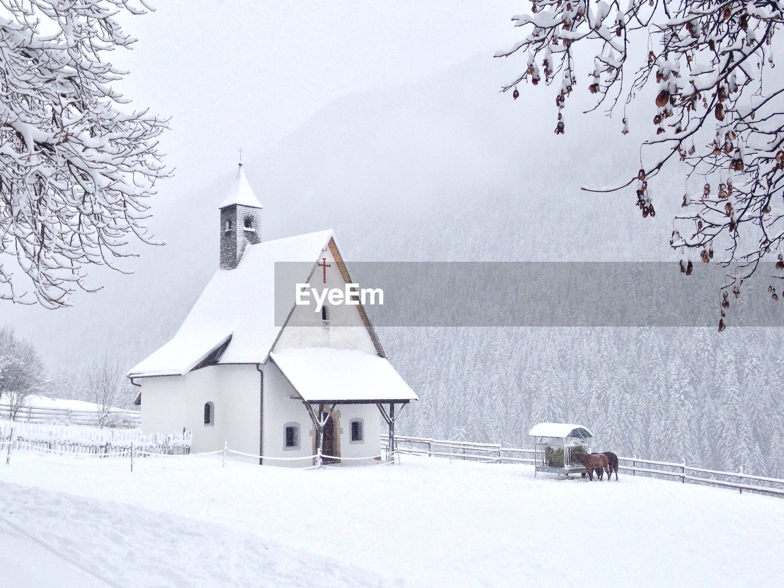 Church on snow covered field against tree mountain