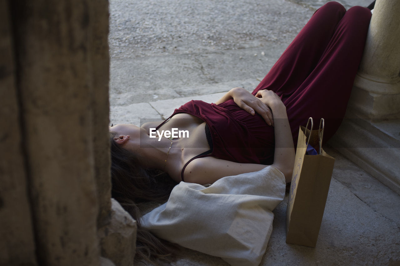 High Angle View Of Sensuous Young Woman With Paper Bag While Resting On Flooring