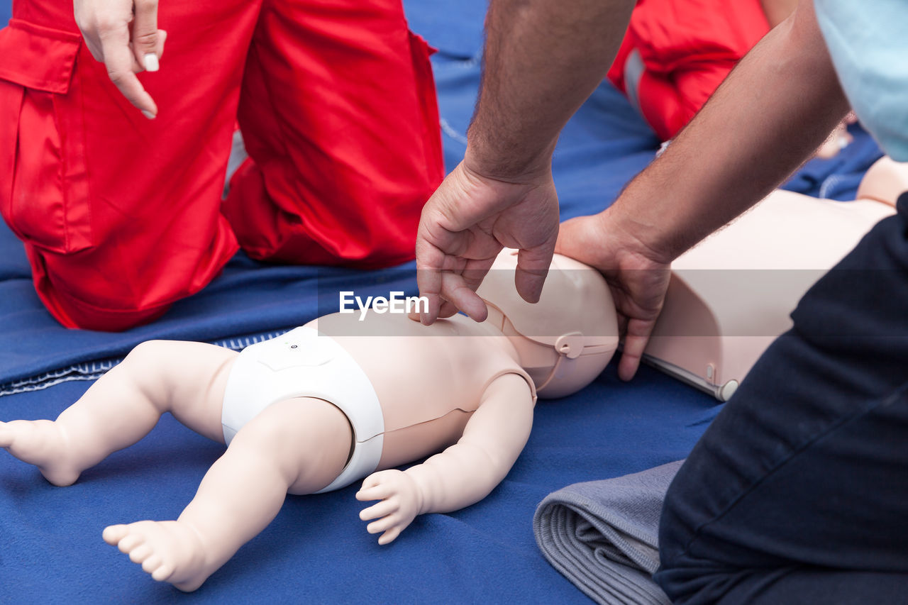 Midsection of trainer with cpr dummy explaining to paramedics
