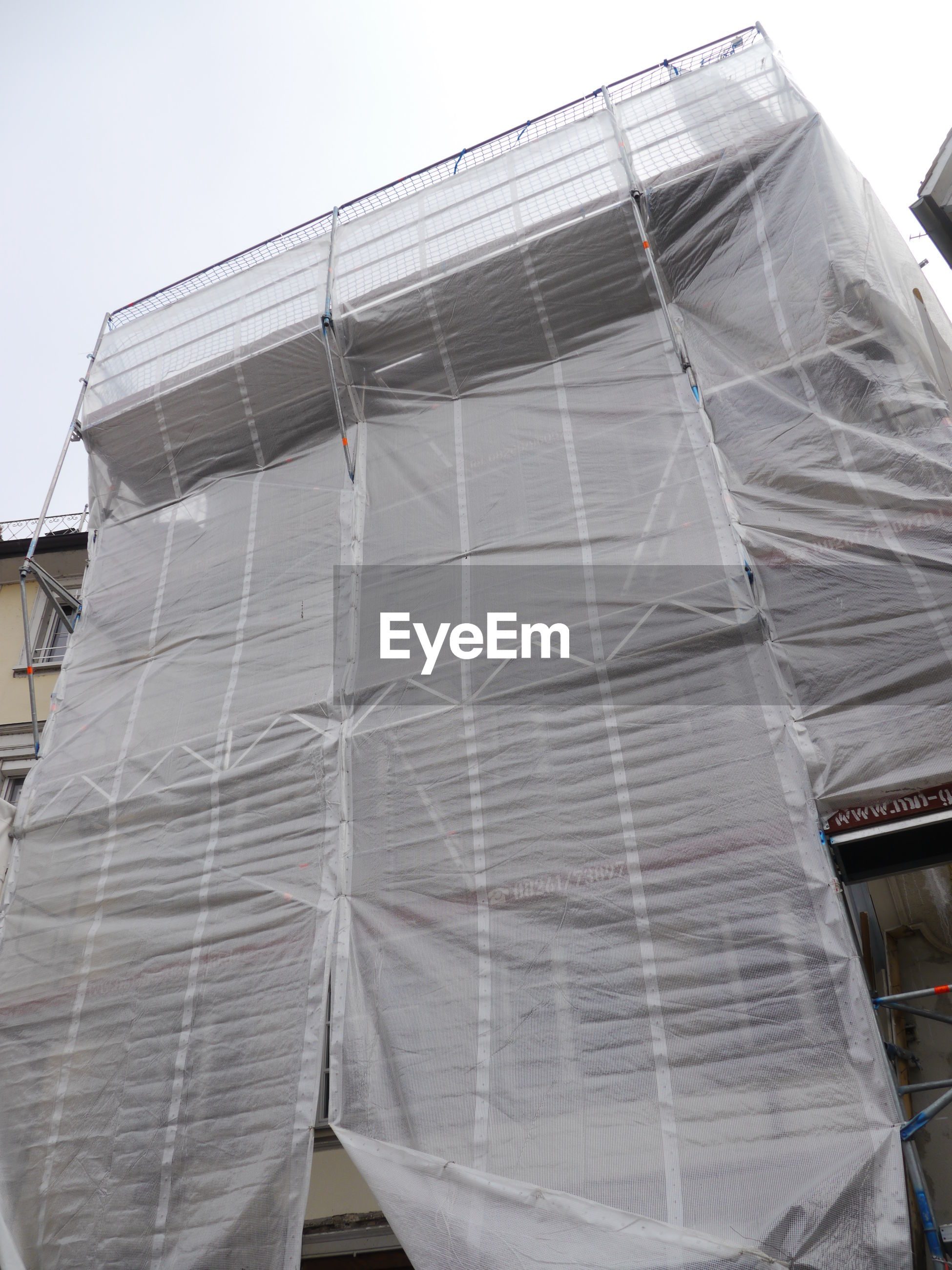 Low angle view of incomplete building covered with plastic