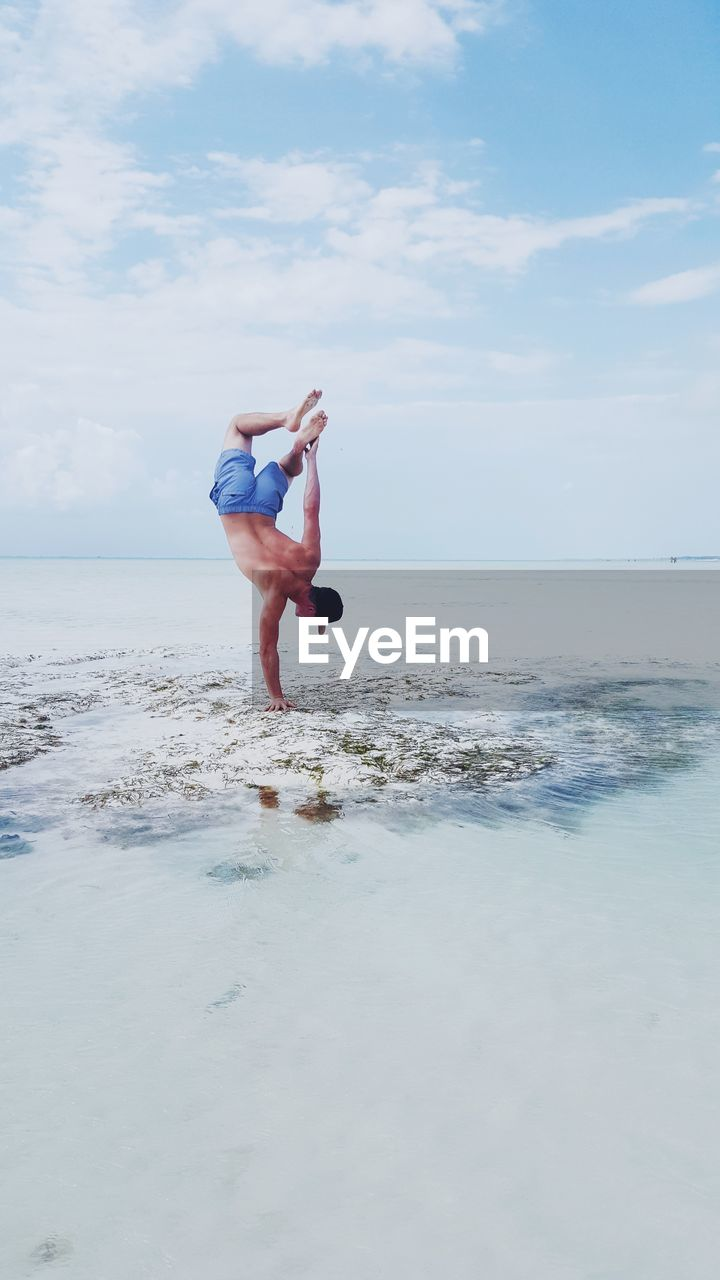 Rear View Of Shirtless Young Man Doing Handstand At Beach Against Sky