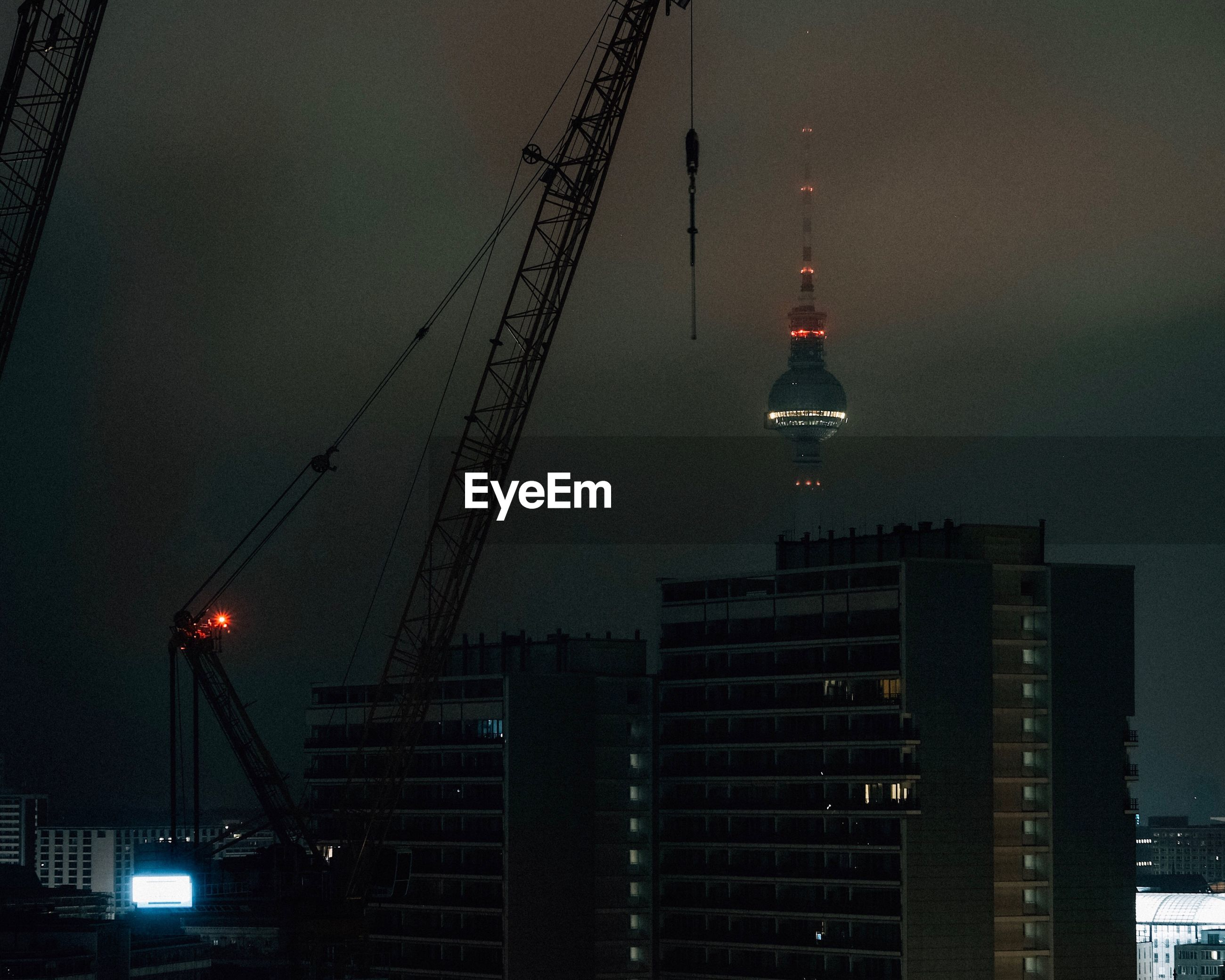 LOW ANGLE VIEW OF CRANE AT NIGHT