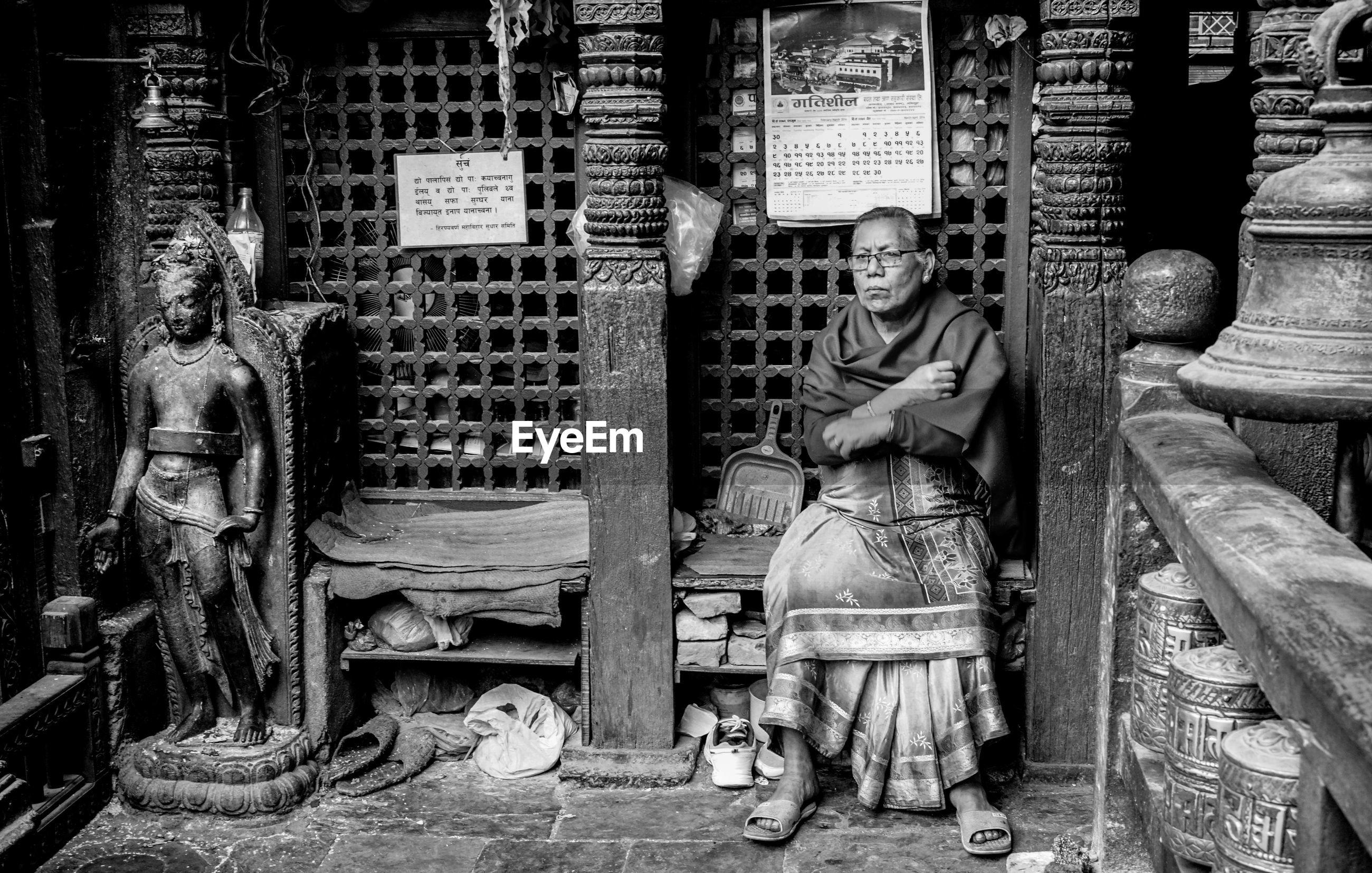 Senior woman sitting in temple