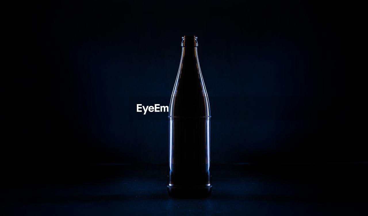 Close-up of beer bottle against black background