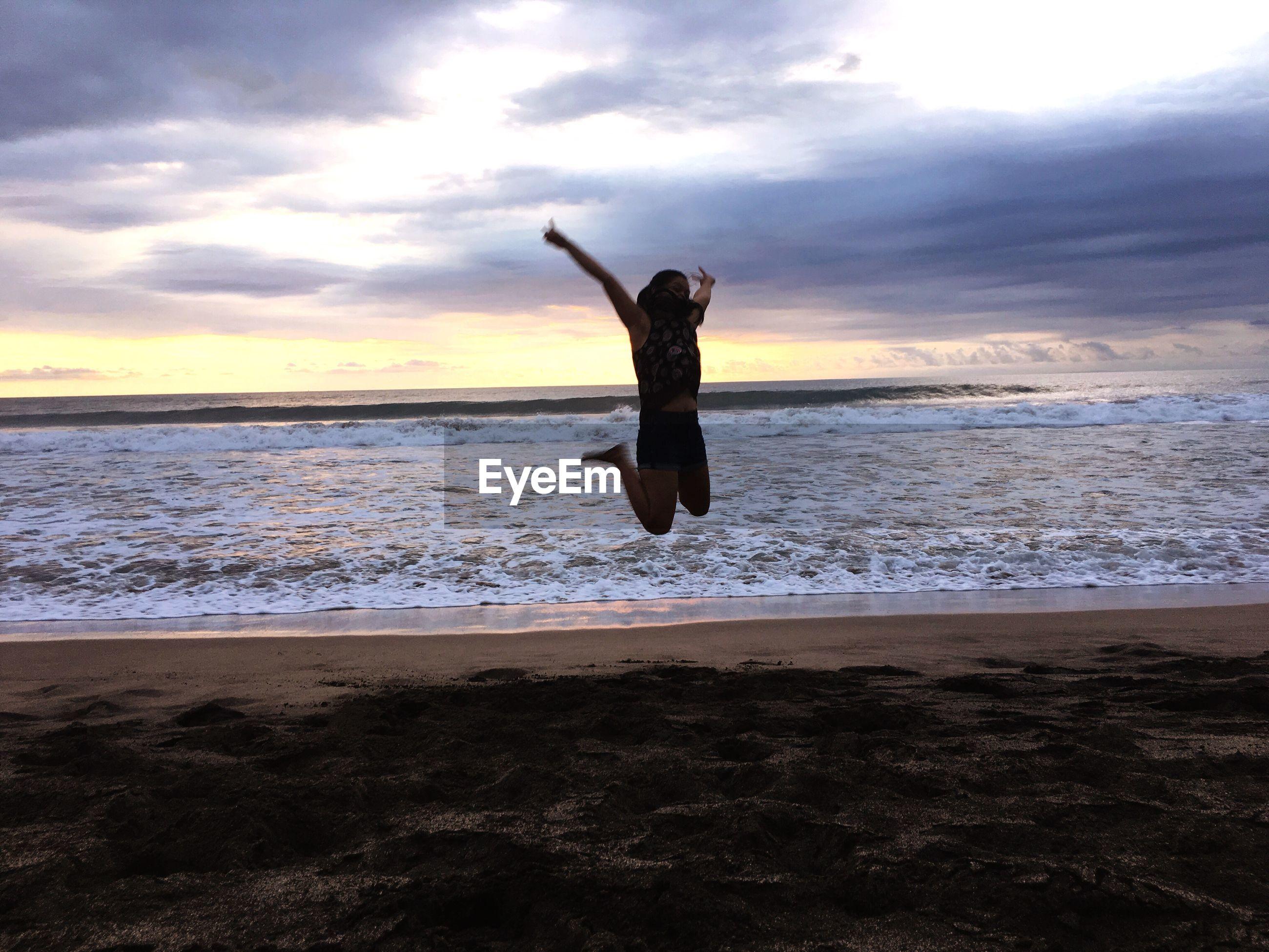 Playful woman jumping at beach during sunset