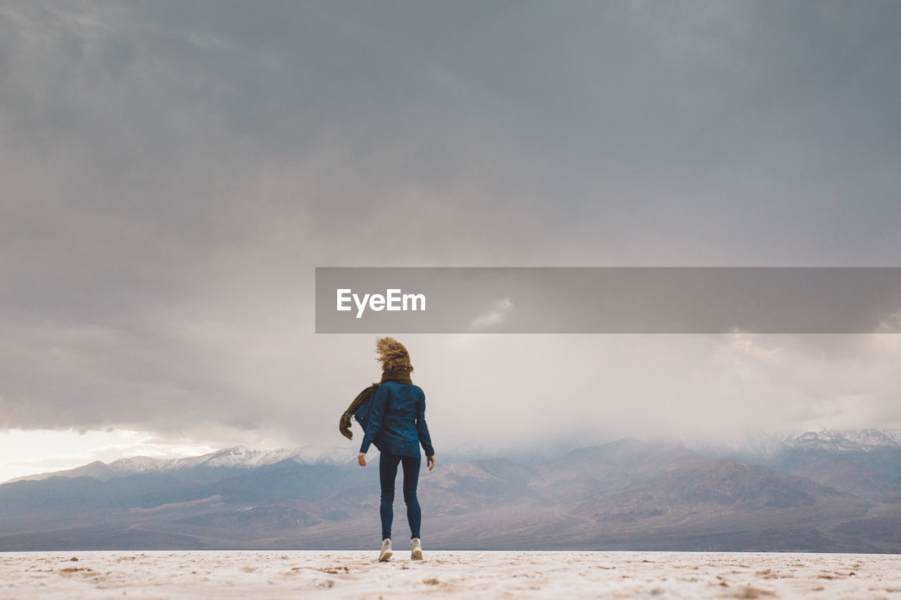 Rear View Of Woman Standing On Field Against Cloudy Sky At Death Valley National Park