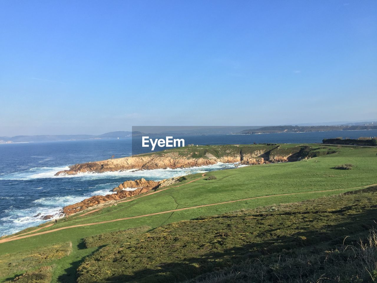 scenics, nature, beauty in nature, sea, water, tranquil scene, grass, tranquility, blue, day, outdoors, green color, sunlight, no people, landscape, sky, beach, mountain, clear sky, horizon over water, blue sky, tree, golf course
