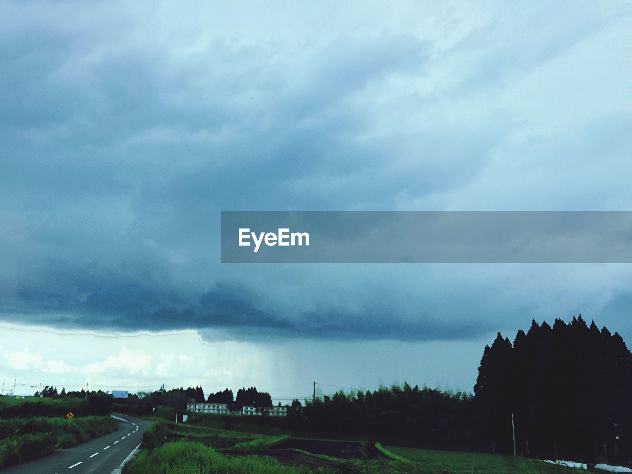 Street by field against cloudy sky