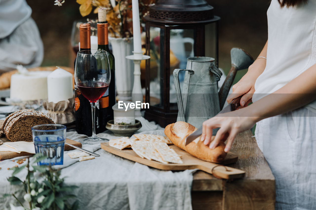 Midsection of woman cutting bread on table