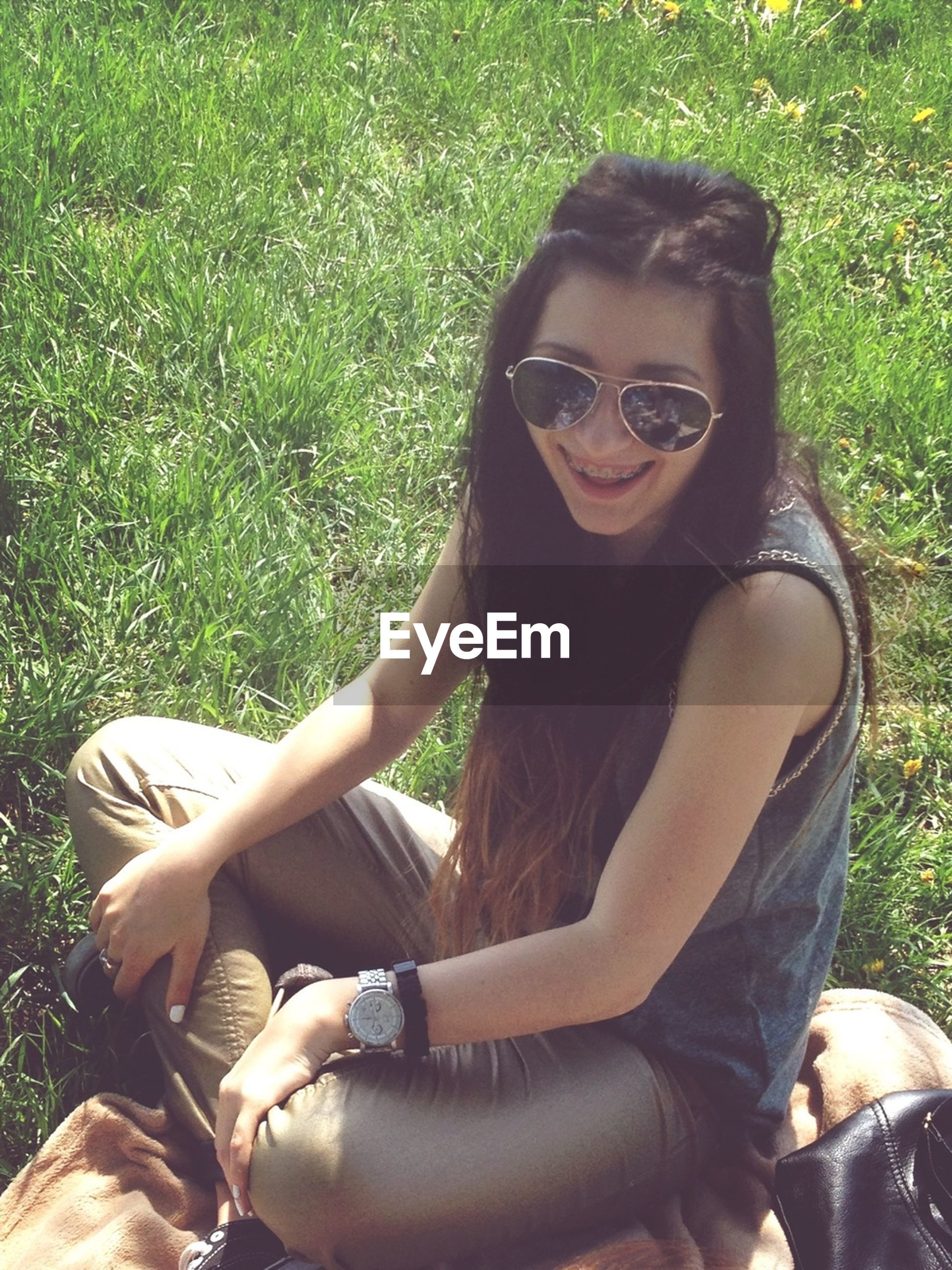 young adult, person, lifestyles, leisure activity, looking at camera, portrait, young women, casual clothing, sitting, grass, smiling, sunglasses, relaxation, field, front view, happiness, sunlight