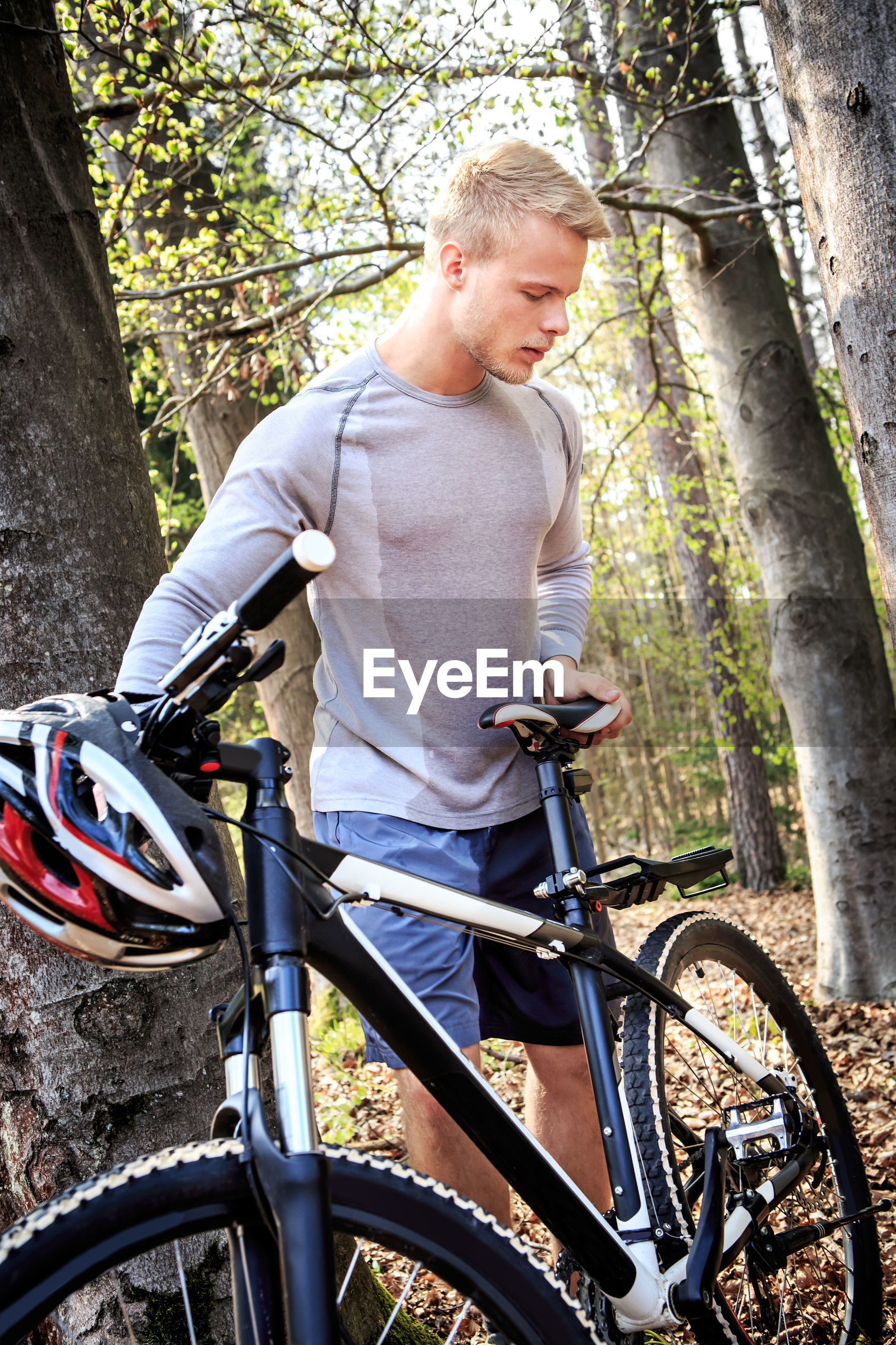 Man standing by bicycle in forest