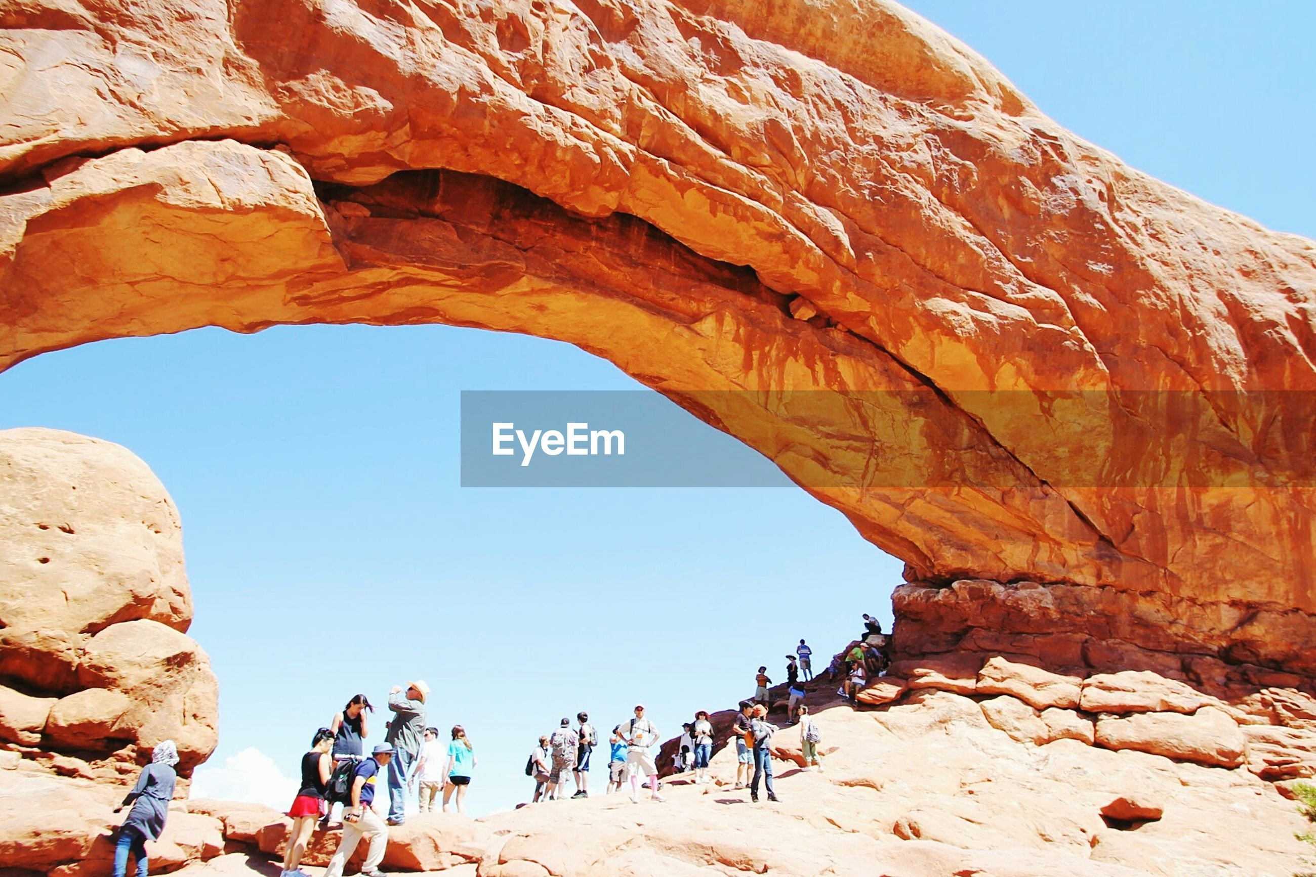 Tourists visiting arches national park against clear sky