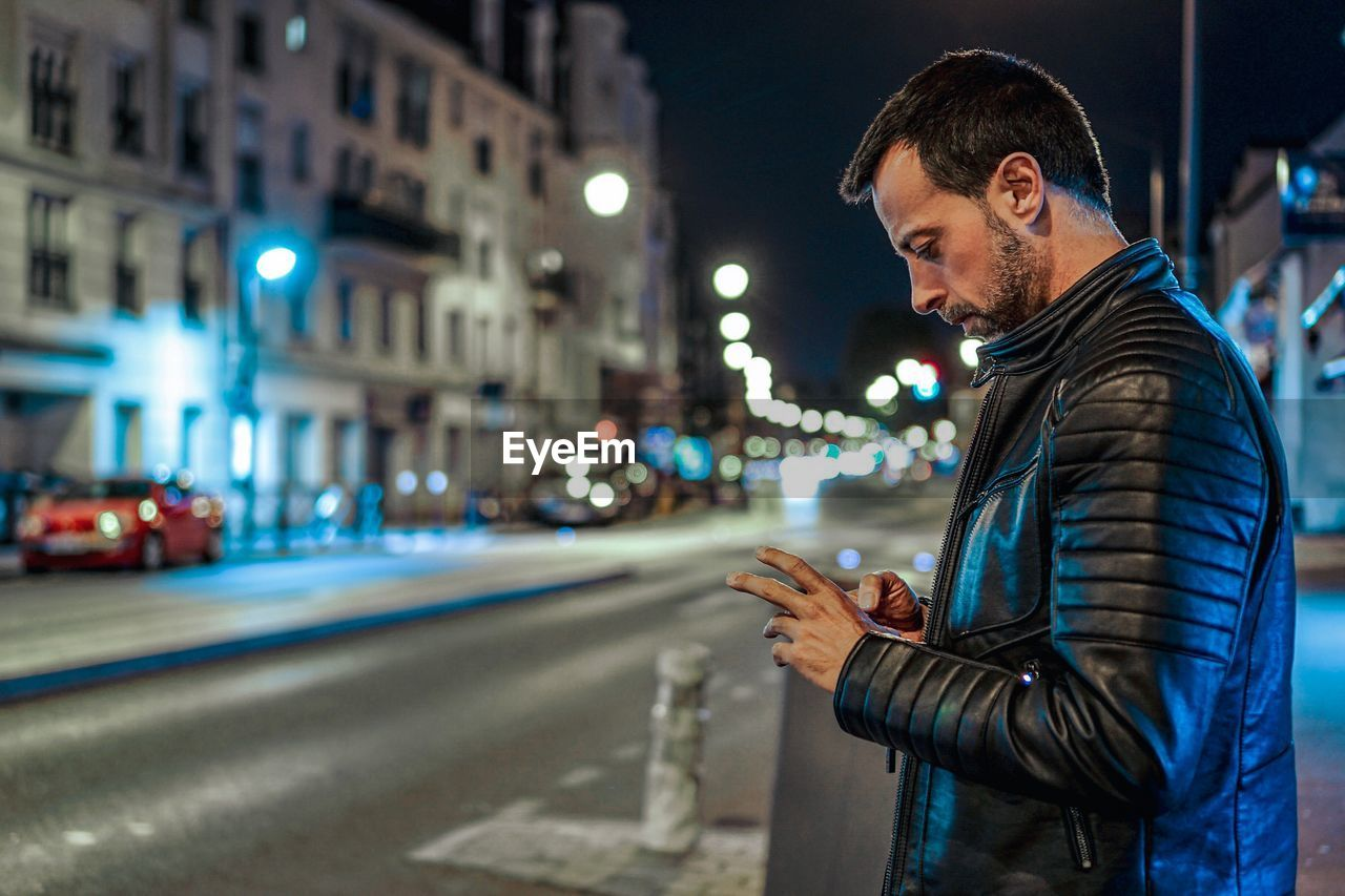 Side view of man using phone by road in city at night