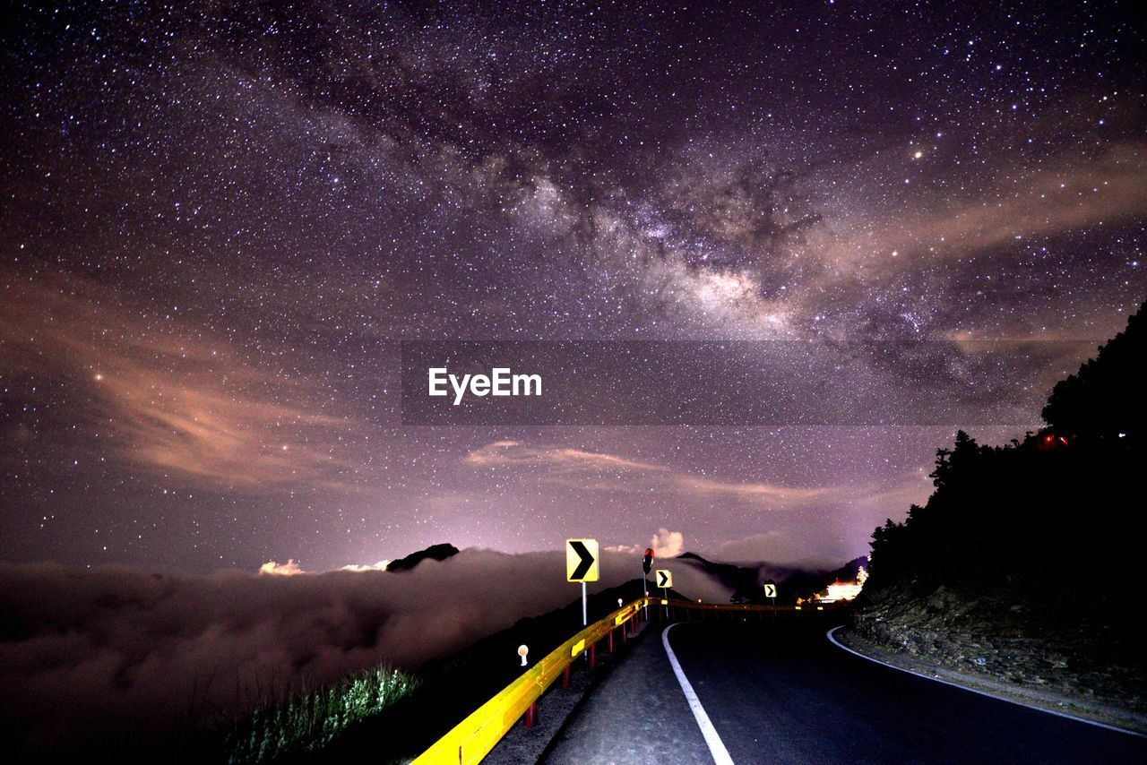 Road Sign Against Sky At Night