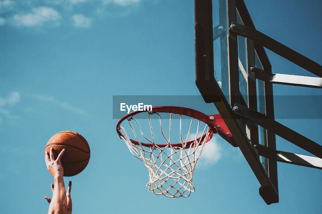 basketball - sport, basketball hoop, sport, sky, net - sports equipment, low angle view, nature, ball, taking a shot - sport, day, basketball - ball, motion, leisure activity, outdoors, making a basket, playing, blue, metal, cloud - sky, no people