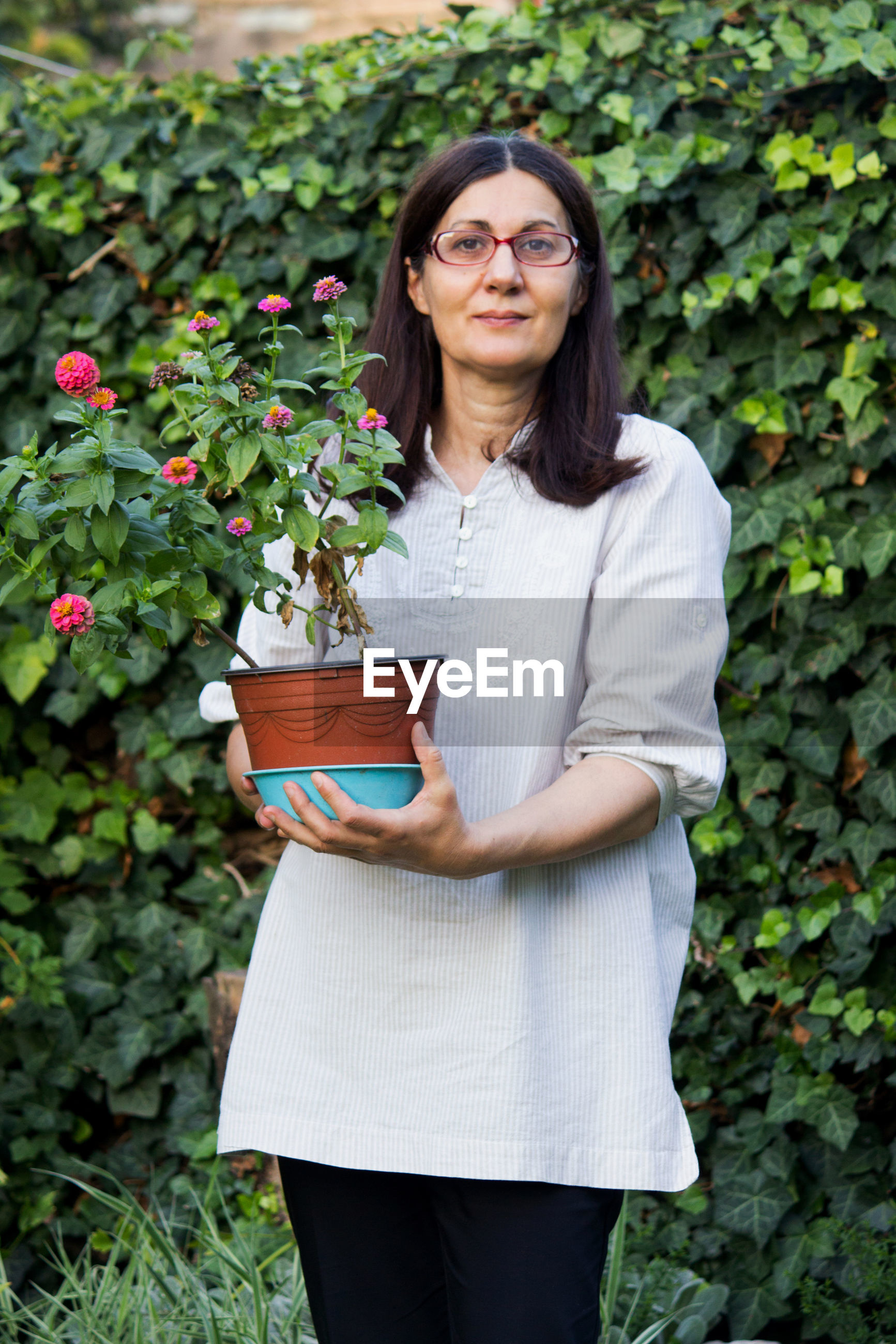 Portrait of woman holding potted plant while standing against plants