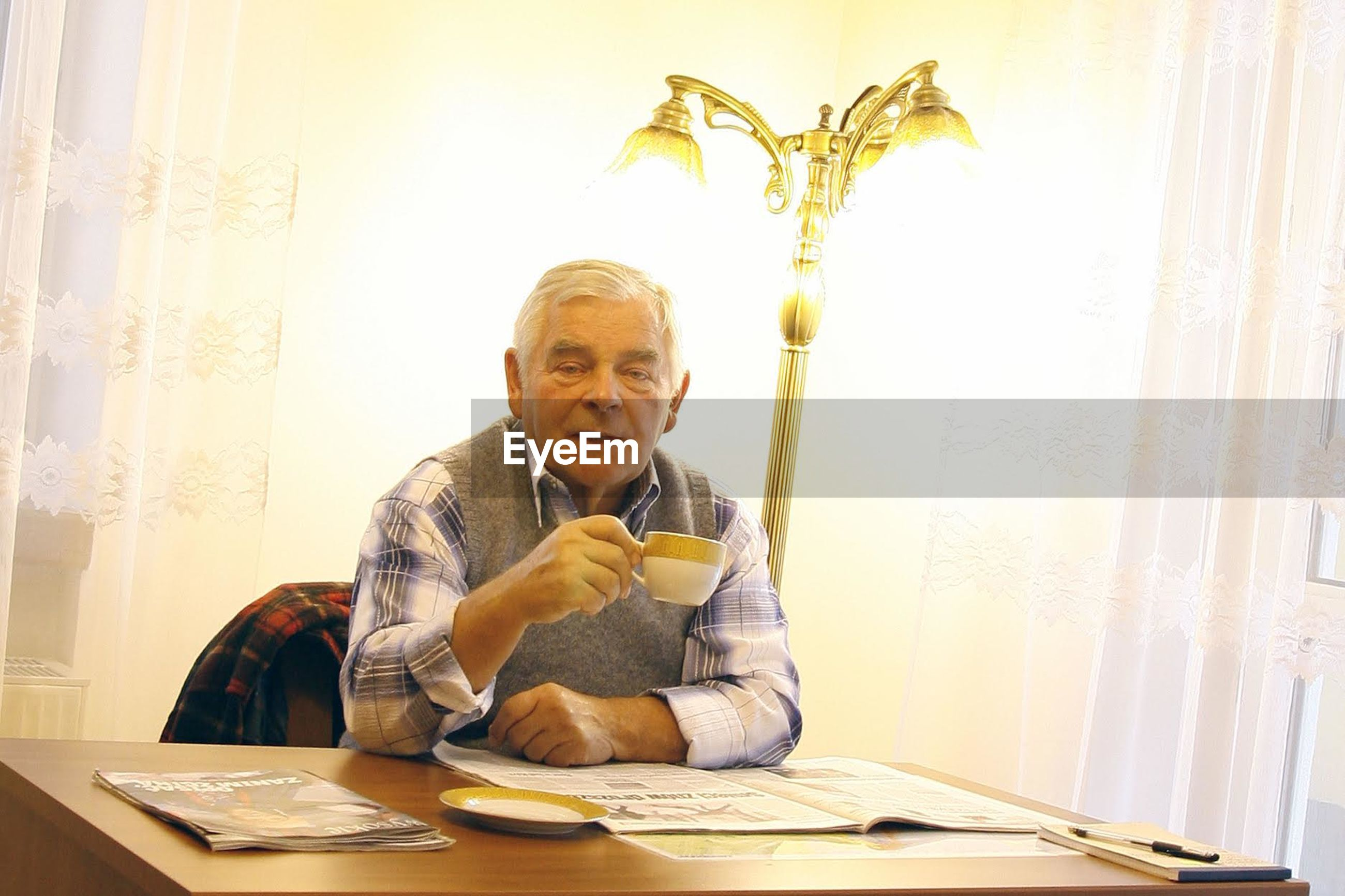 Portrait of senior man drinking coffee at table