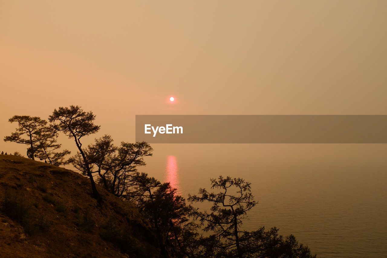 Scenic view of lake baikal against sky during sunset