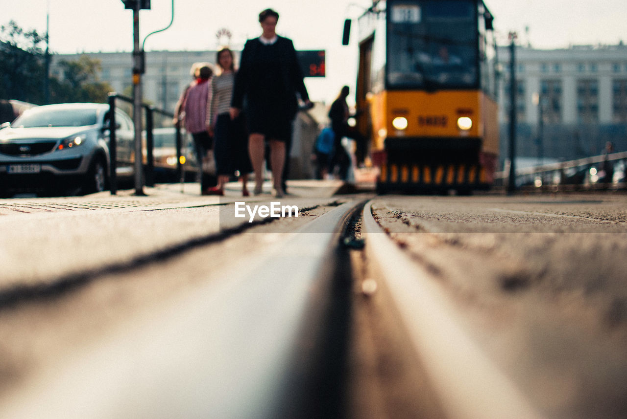 Surface Level Of People Walking By Tram On Railroad Tracks
