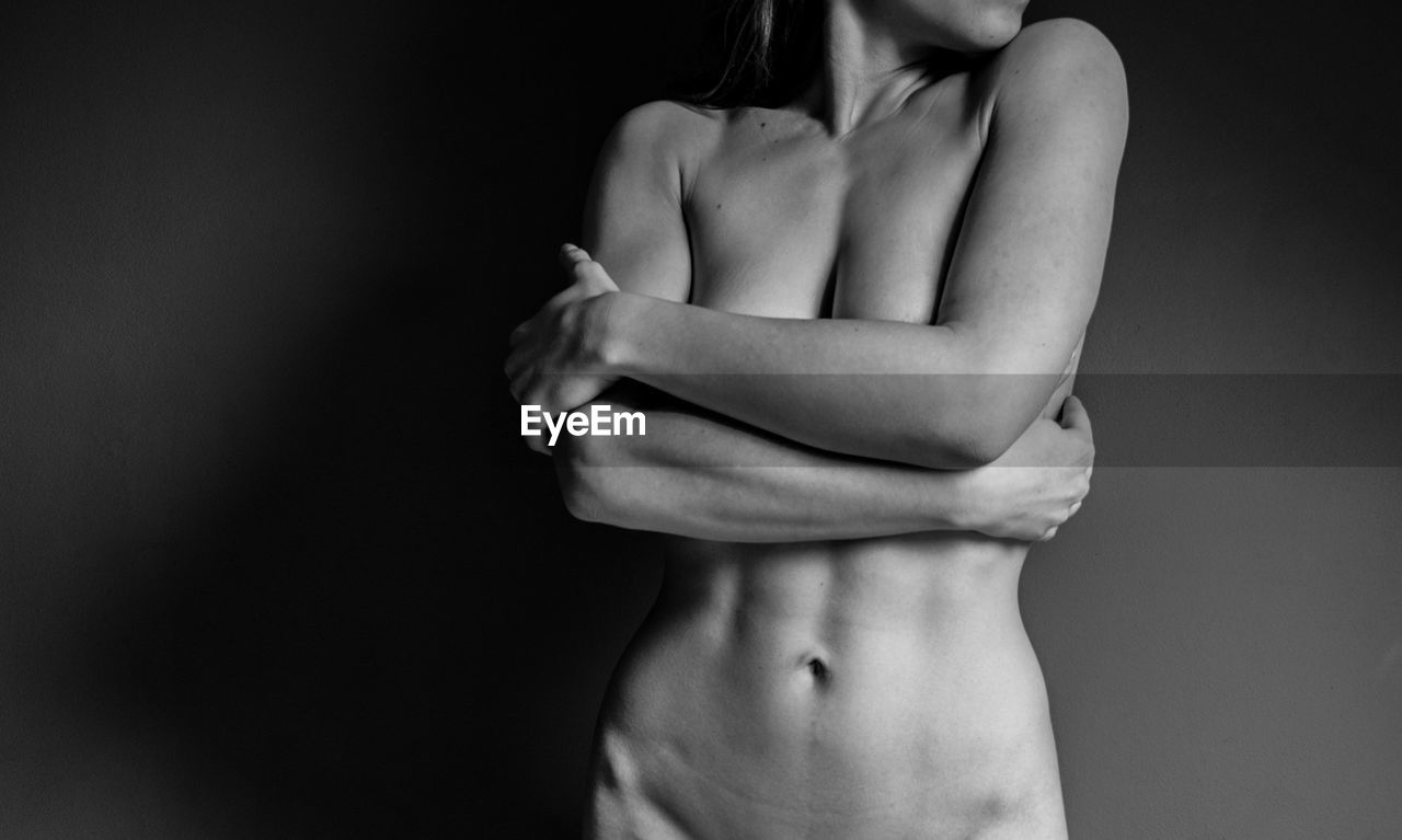 Midsection of naked young woman against black background