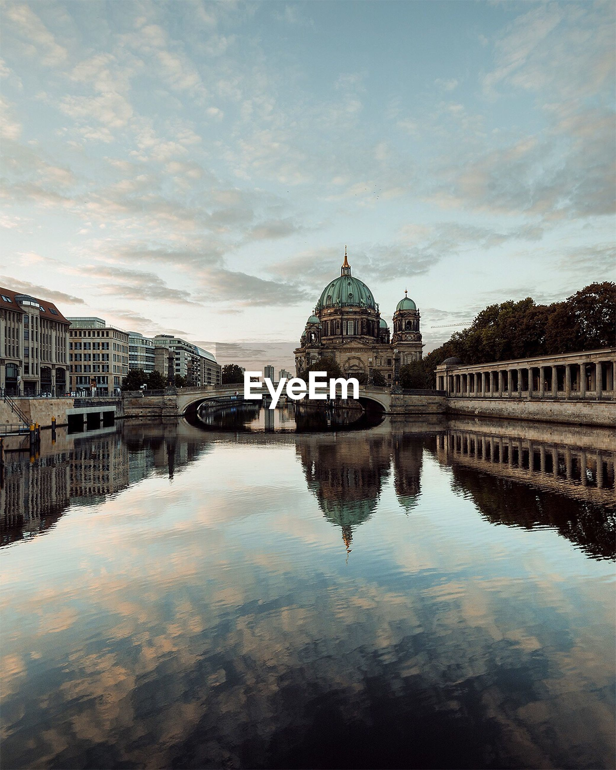 Reflection of berlin cathedral and bridge on canal during sunset