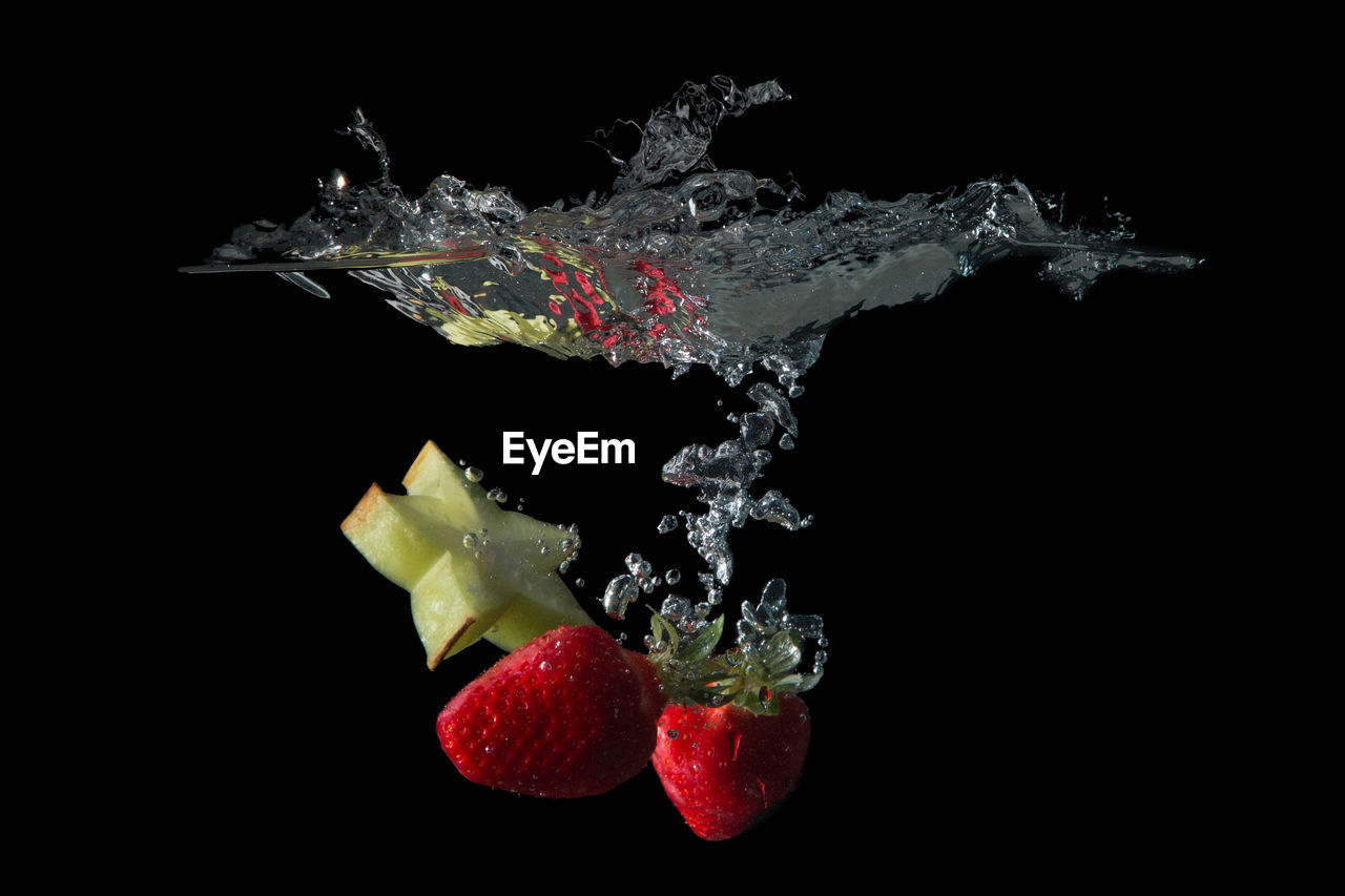 Close-Up Of Strawberries In Water Against Black Background